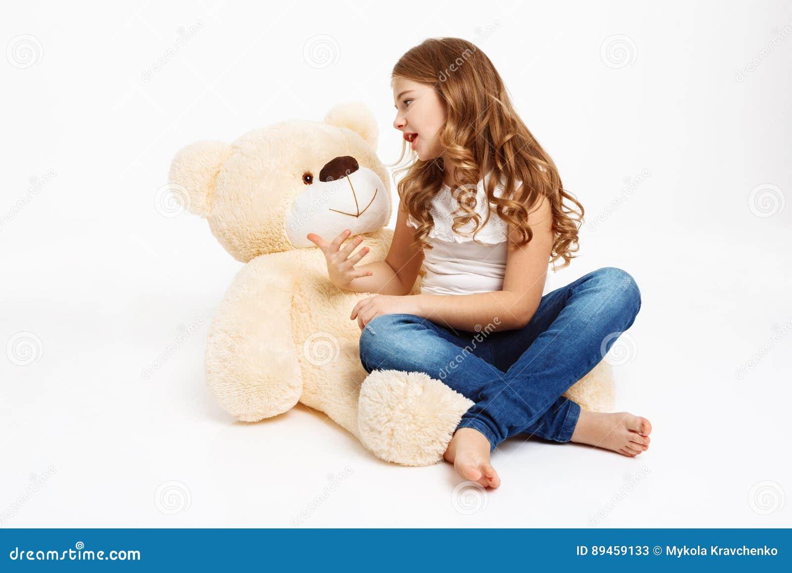 Belle fille s asseyant sur le plancher avec l ours de jouet, racontant l histoire
