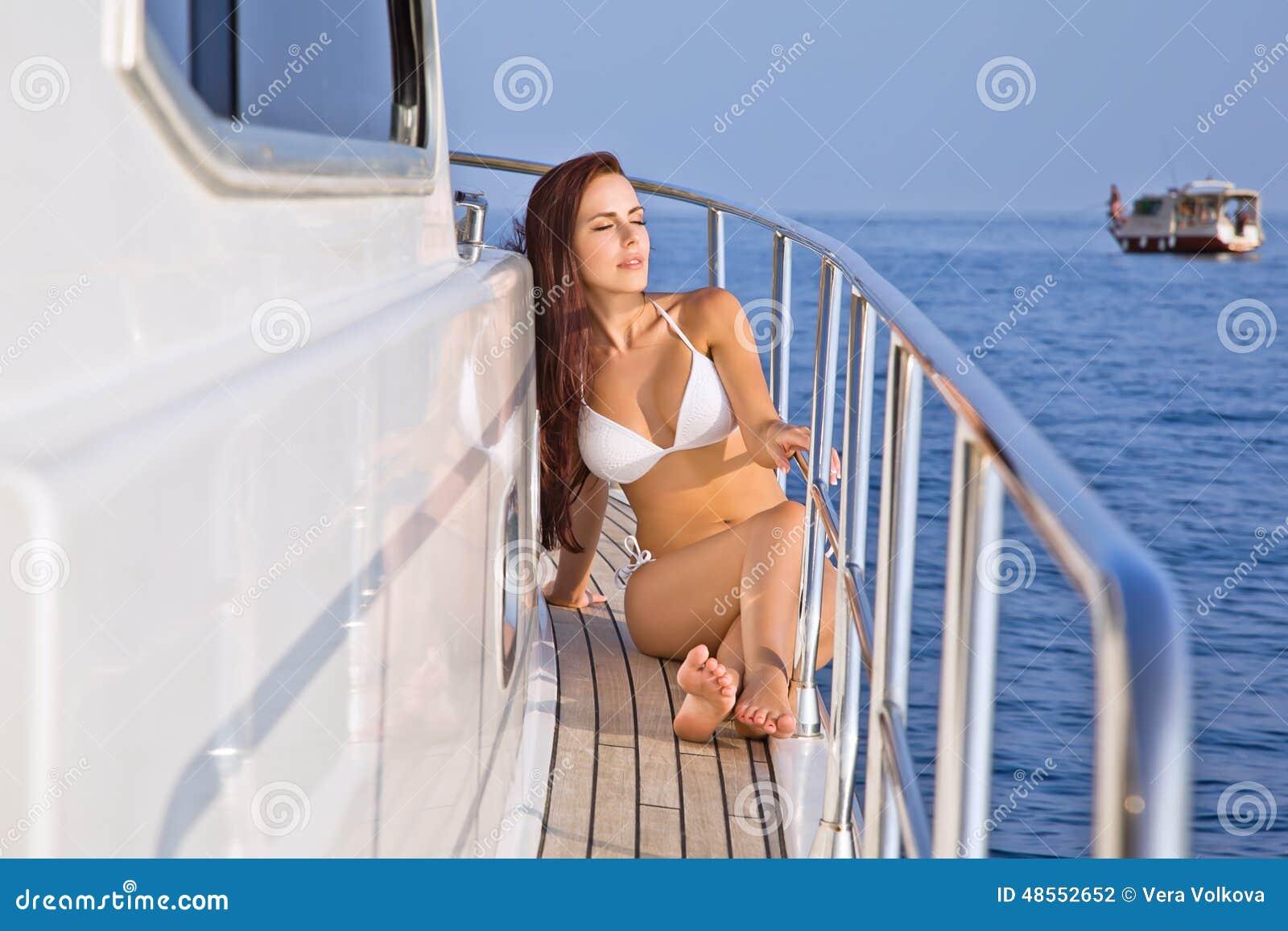 Belle fille sur un yacht à la lumière du soleil