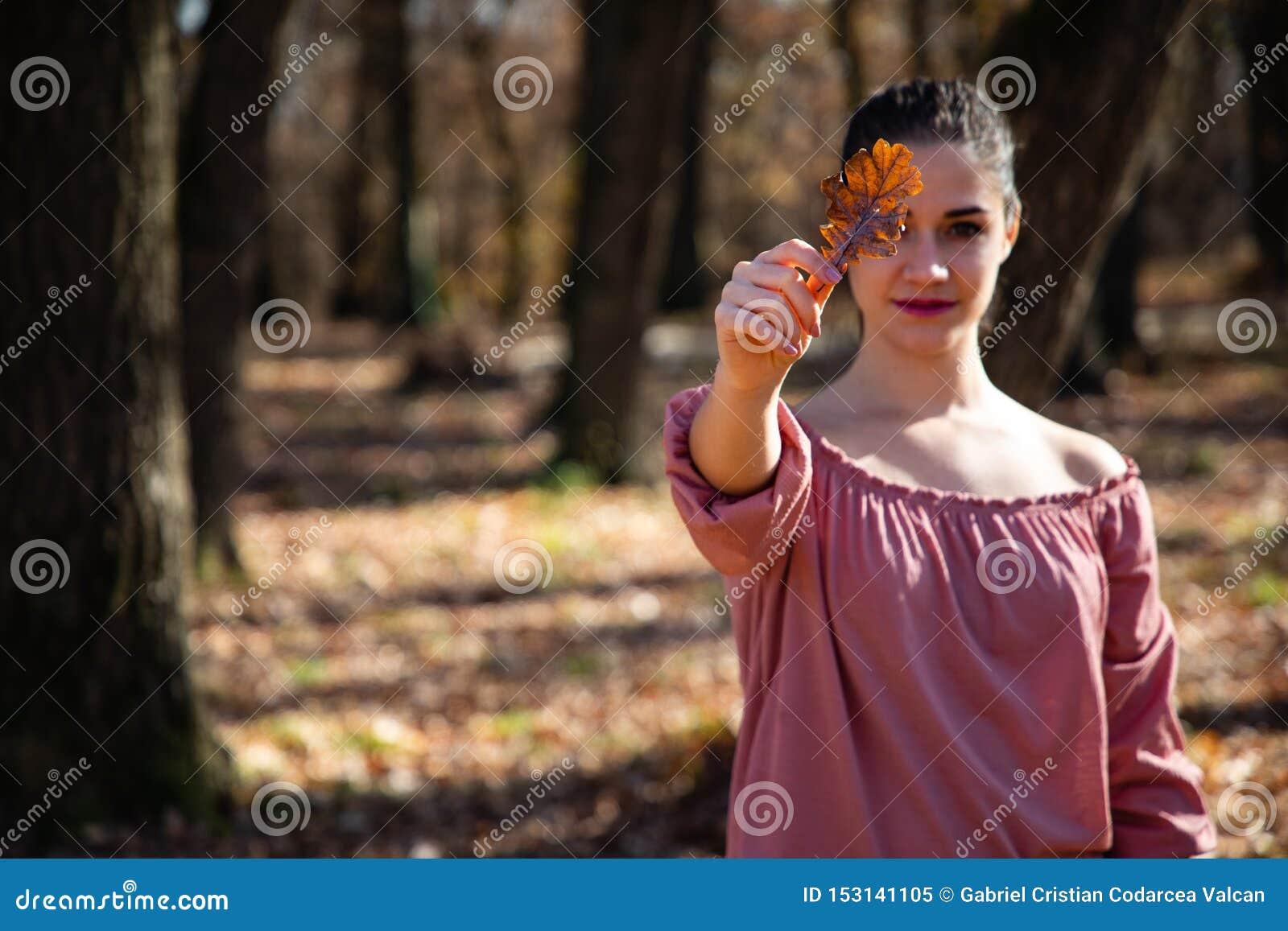 Belle fille tenant une feuille brune couvrant son oeil