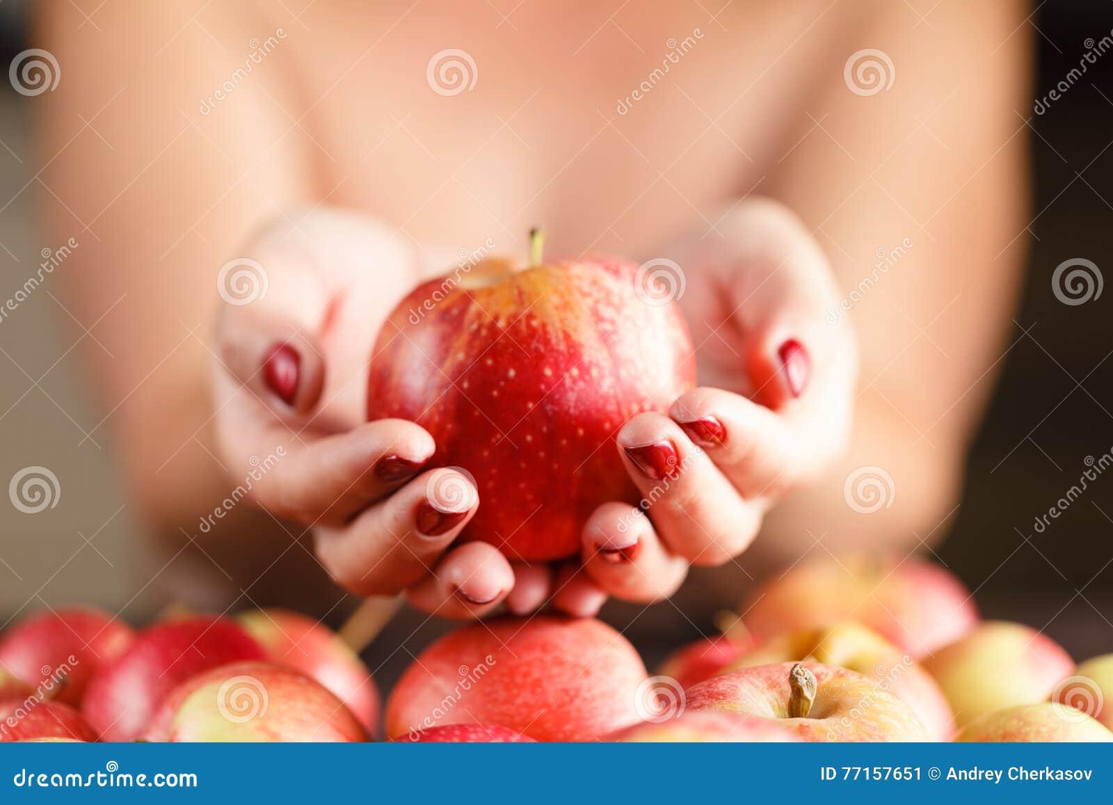 Belle fille tenant une pomme dans sa main La fille offre