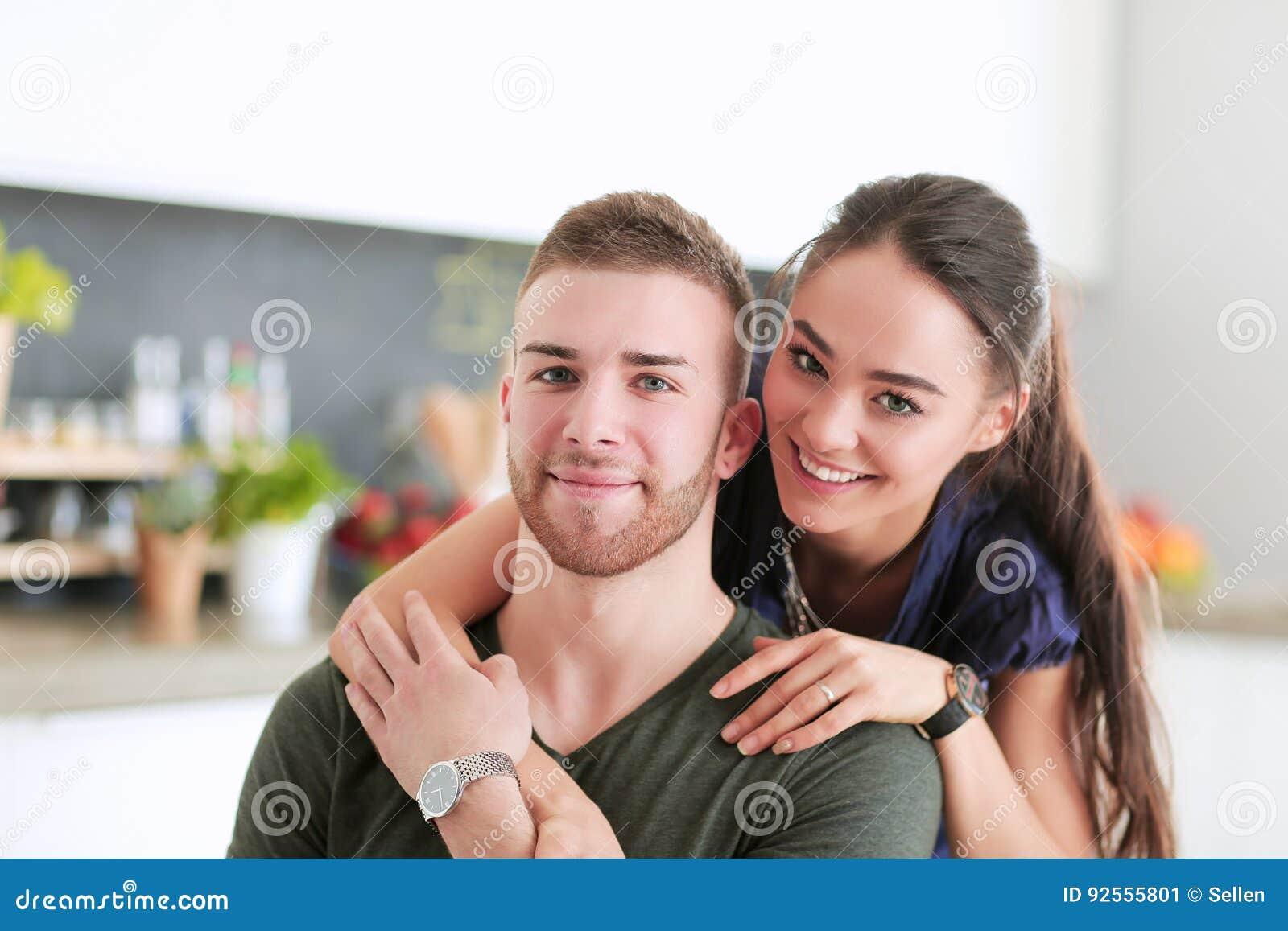 Belle giovani coppie che si siedono nella cucina a casa