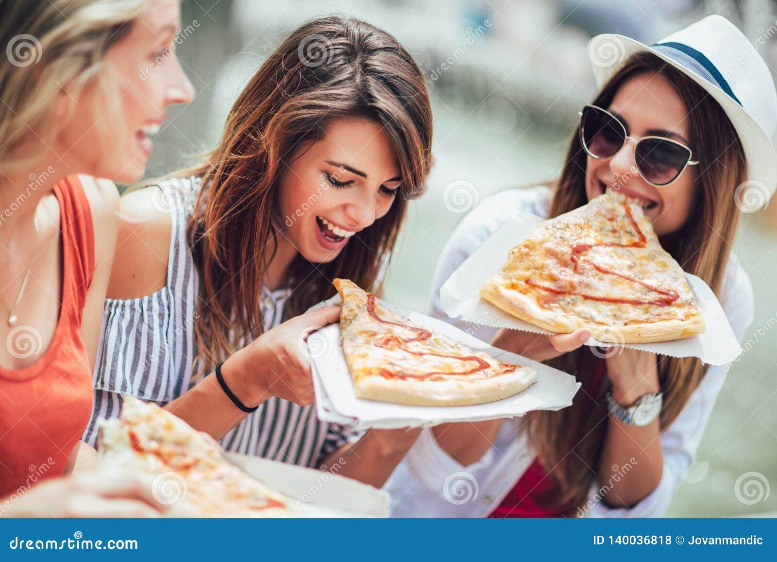 Belle giovani donne che mangiano pizza dopo la compera, divertendosi insieme