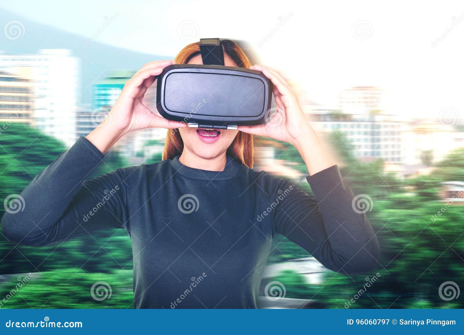 Belle jeune brune avec la réalité virtuelle de port de longs cheveux