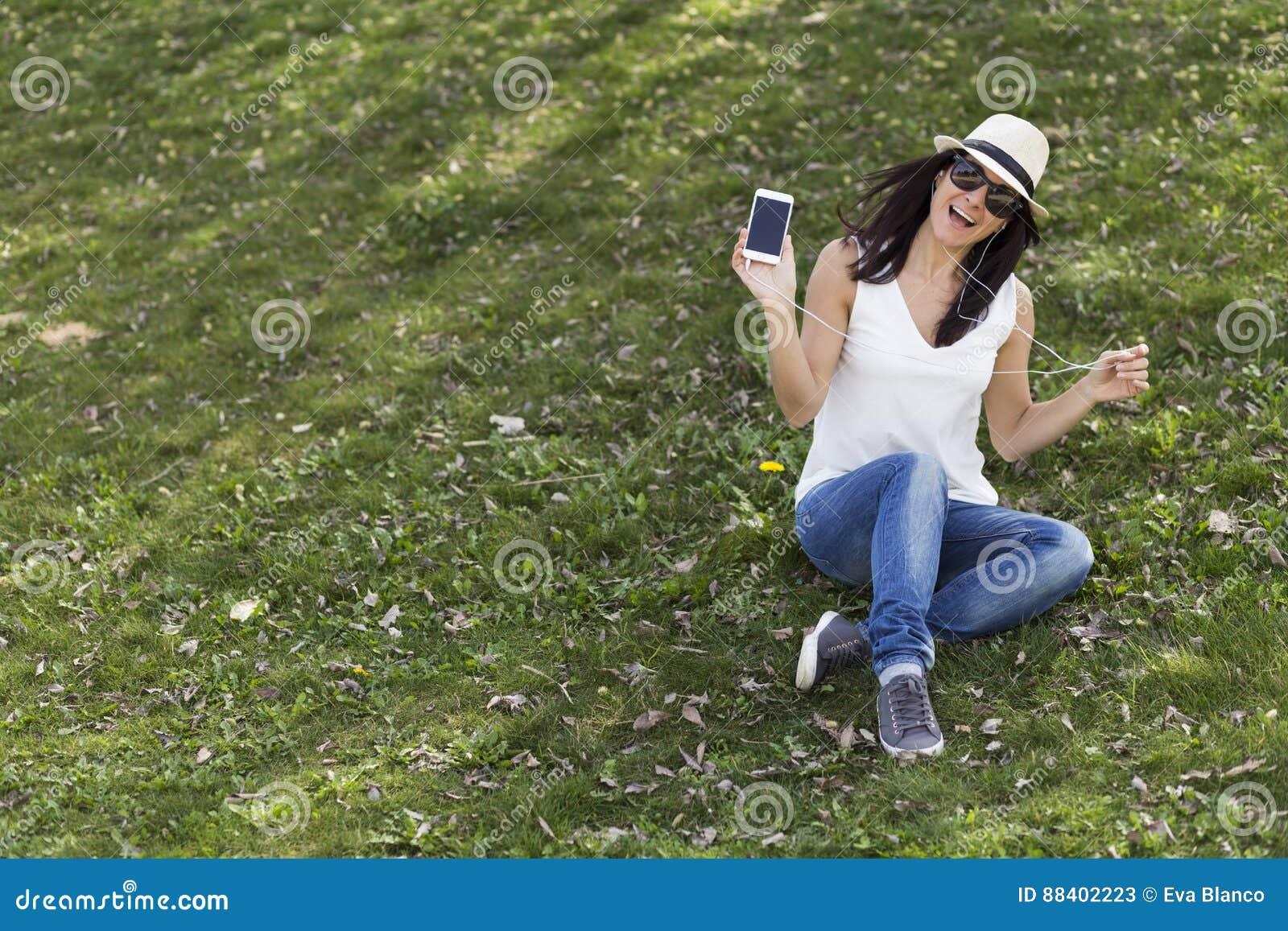 Belle jeune femme écoutant la musique à son téléphone intelligent elle
