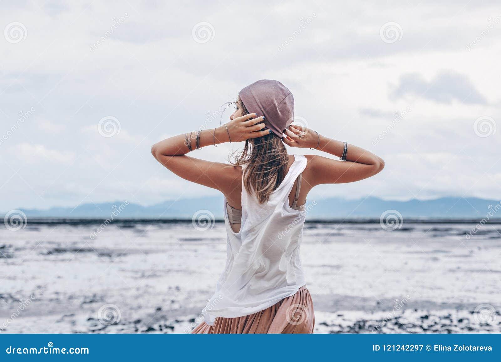 Belle jeune femme élégante dans la jupe rose sur la plage