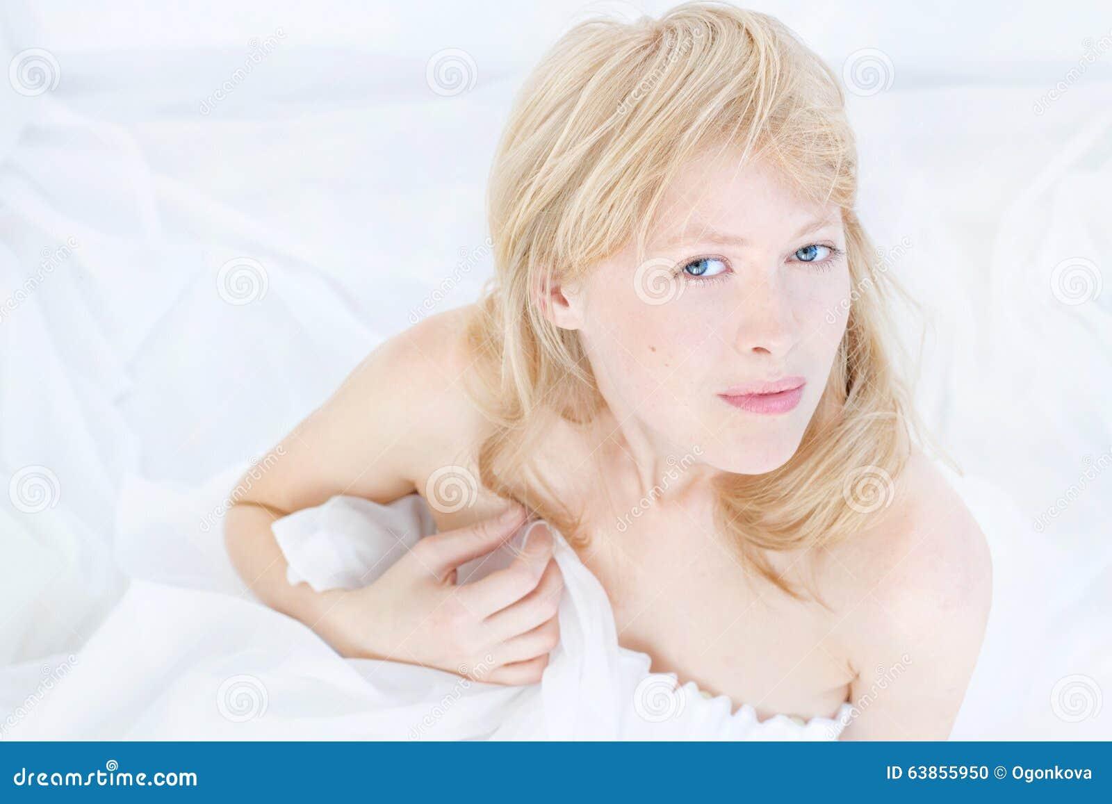Belle jeune femme attirante (fin vers le haut de visage) dans la robe blanche avec la peau saine caucasienne, cheveux blonds, yeu