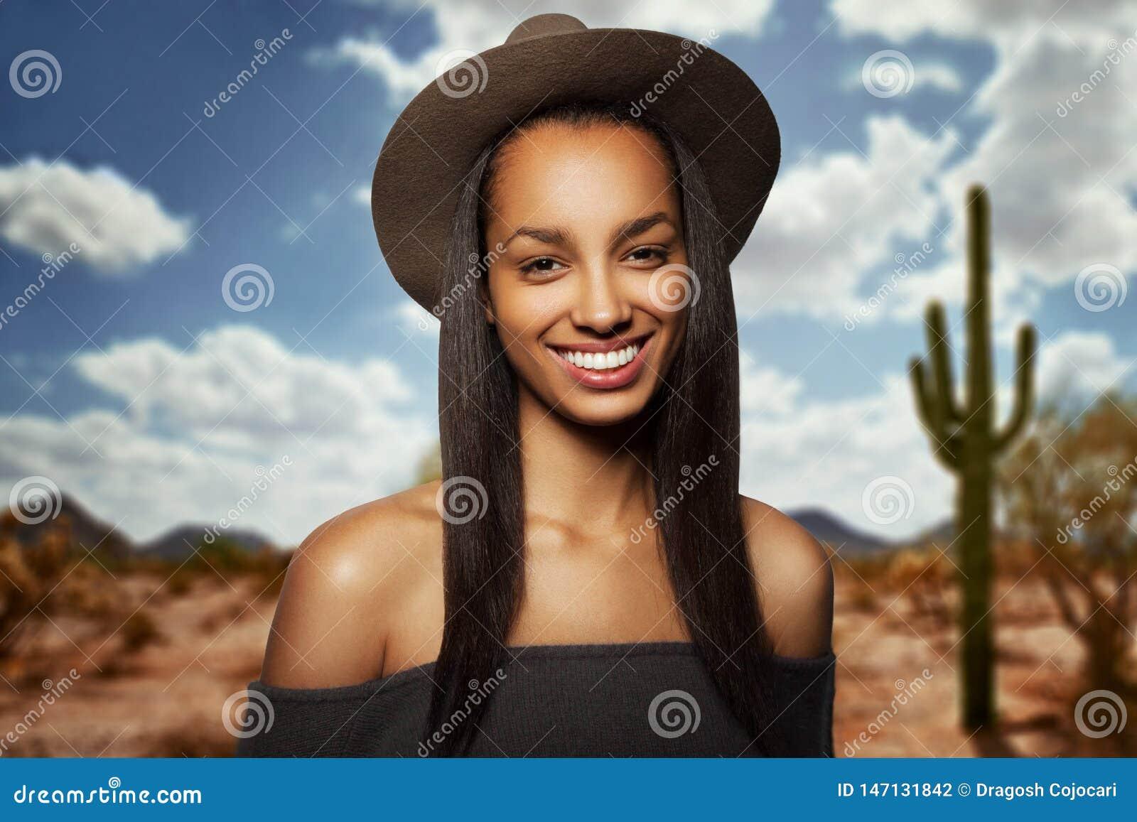 Belle jeune femme avec le chapeau brun, longs cheveux, souriant, avec les épaules nues, d isolement sur un fond trouble de désert