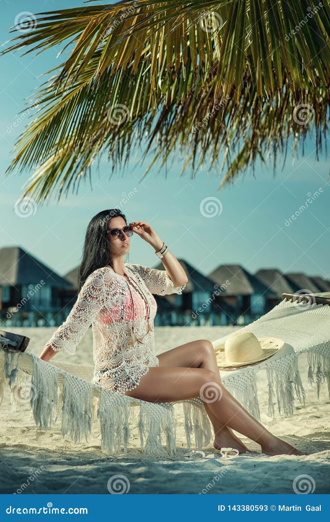 Belle jeune femme avec le chapeau sur la plage blanche, beau paysage avec la femme en Maldives, paradis tropical