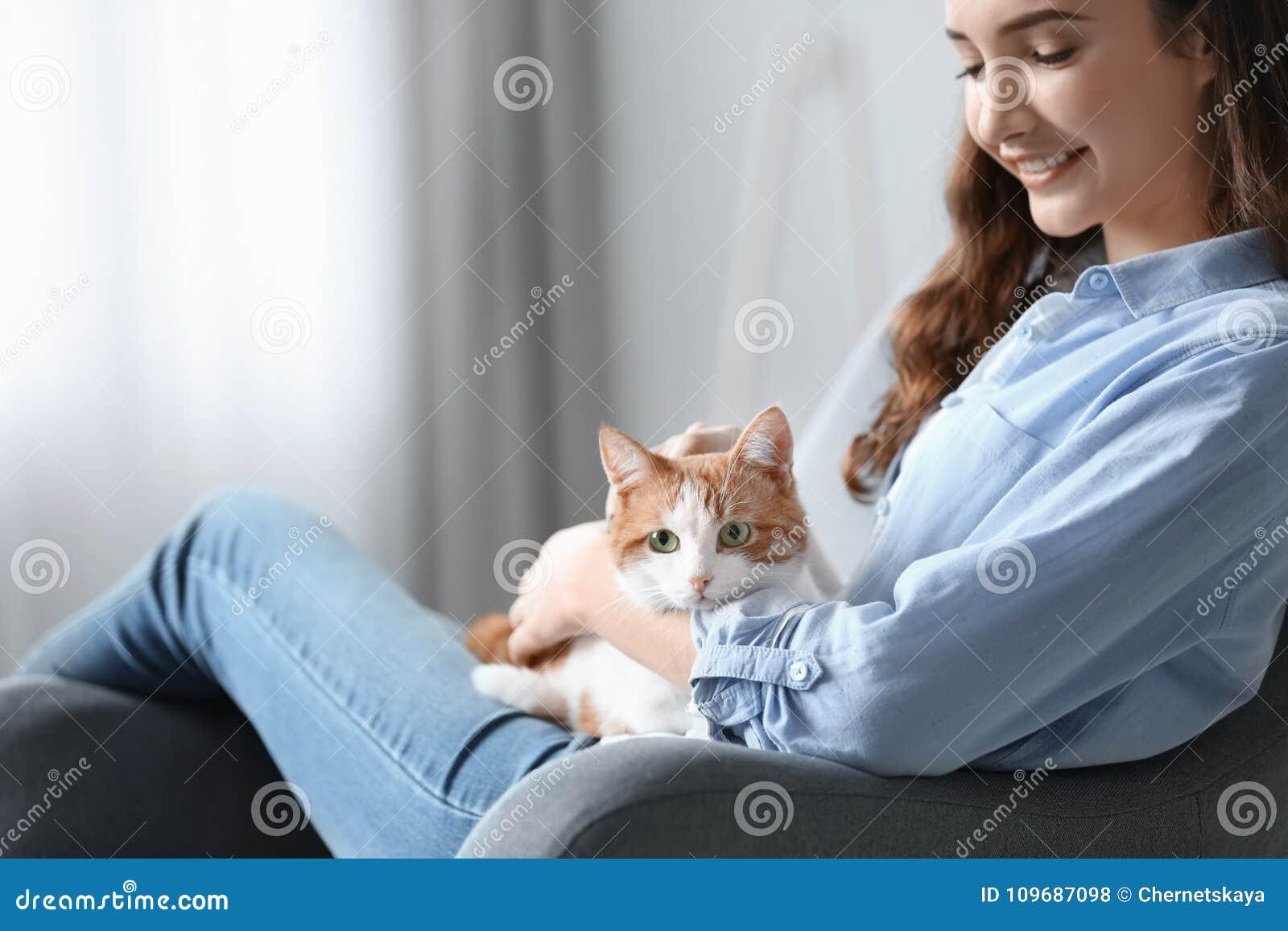 Belle jeune femme avec le chat mignon dans le fauteuil