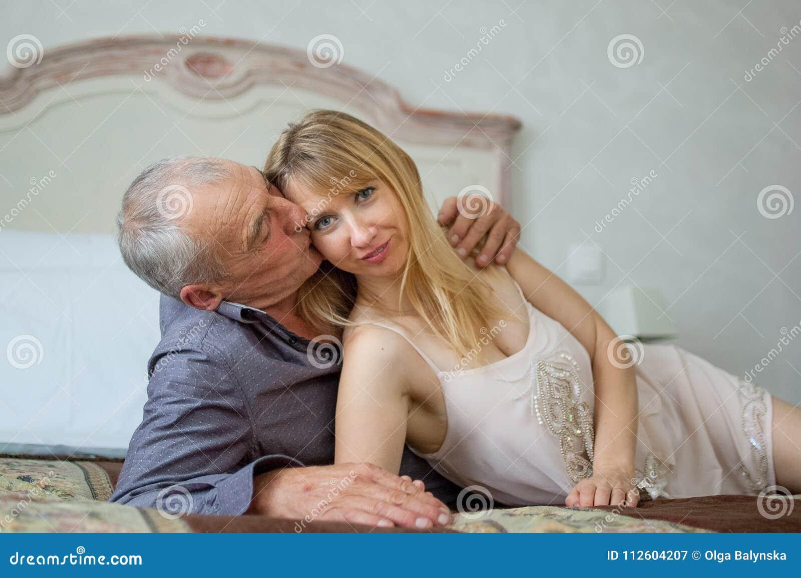 Belle jeune femme avec son amant supérieur se trouvant sur le lit Homme embrassant sa amie Portrait de beaux couples heureux