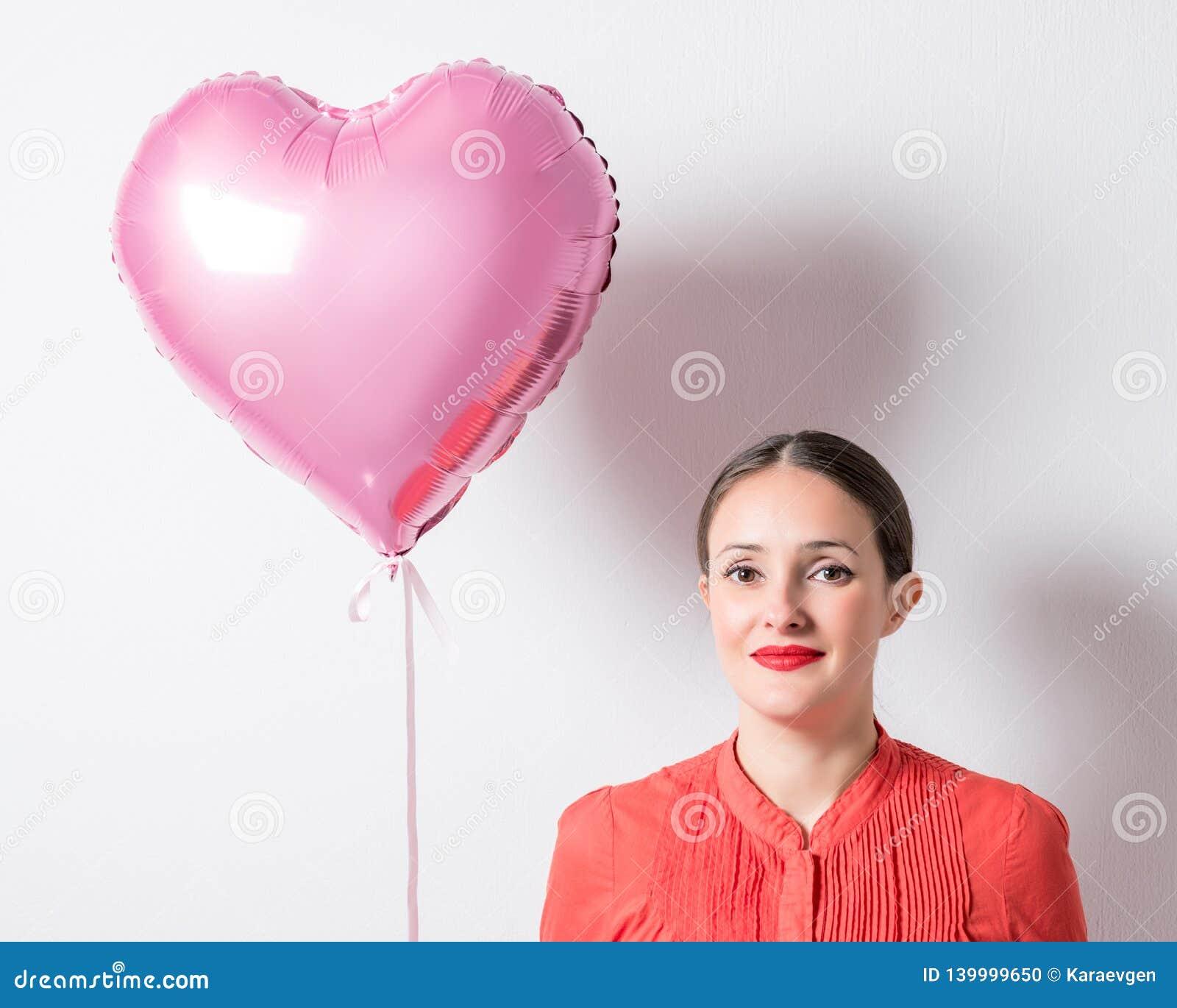 Belle jeune femme avec un ballon en forme de coeur sur un fond lumineux Concept de jour du ` s de Valentine