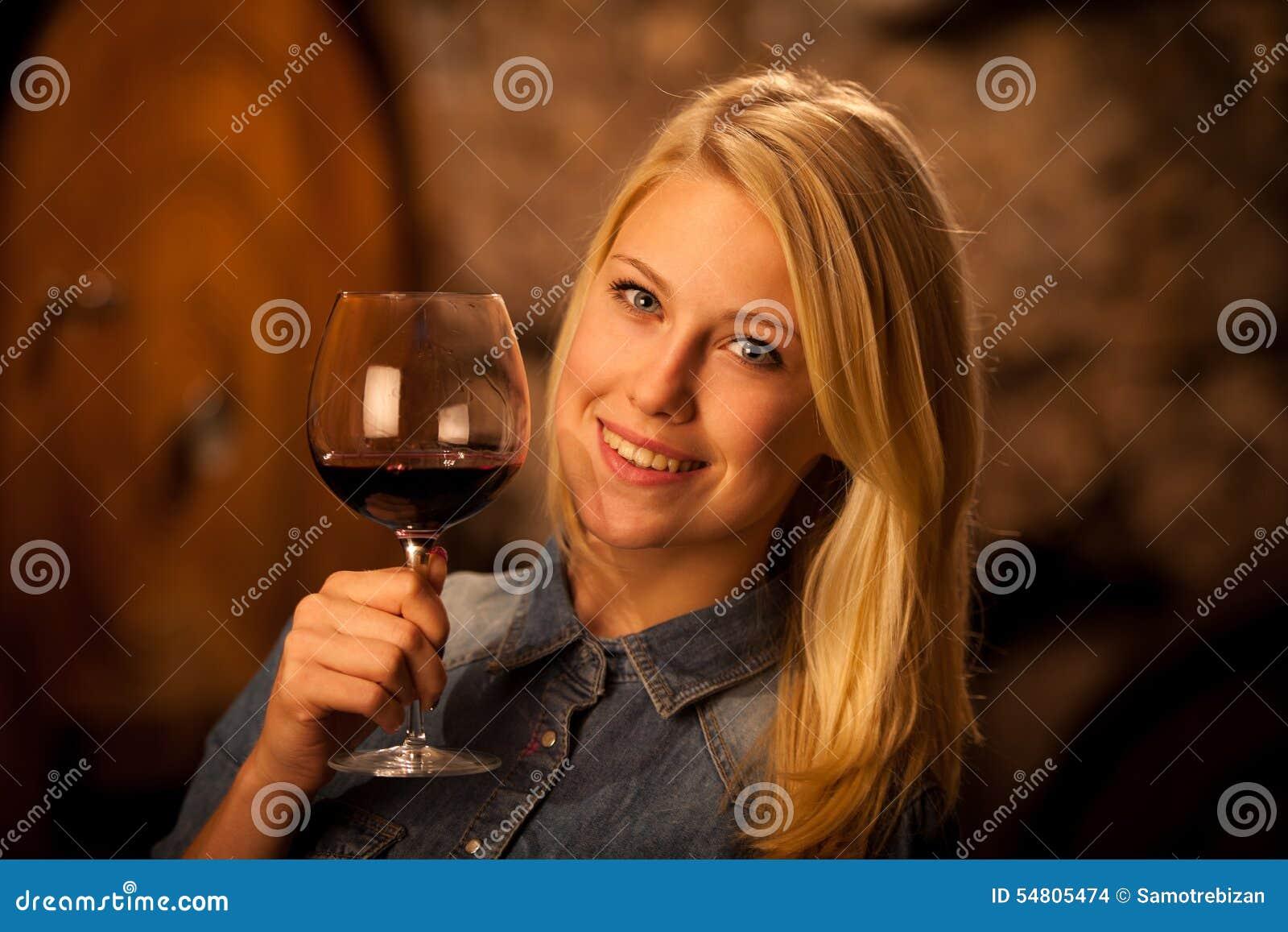 Belle jeune femme blonde goûtant le vin rouge dans une cave