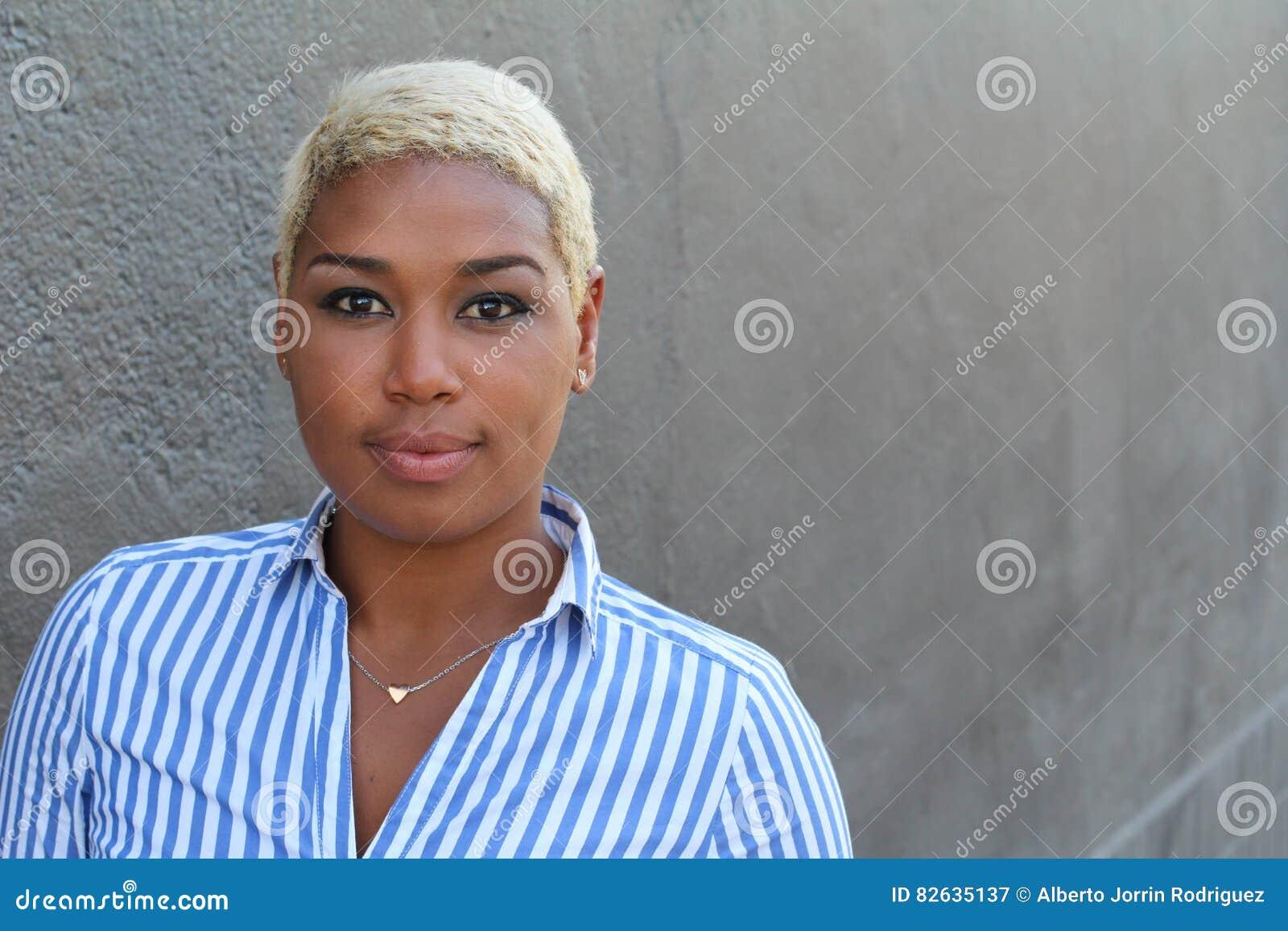 Belle jeune femme d Afro-américain avec les cheveux blonds teints courts regardant l appareil-photo avec une expression neutre dé