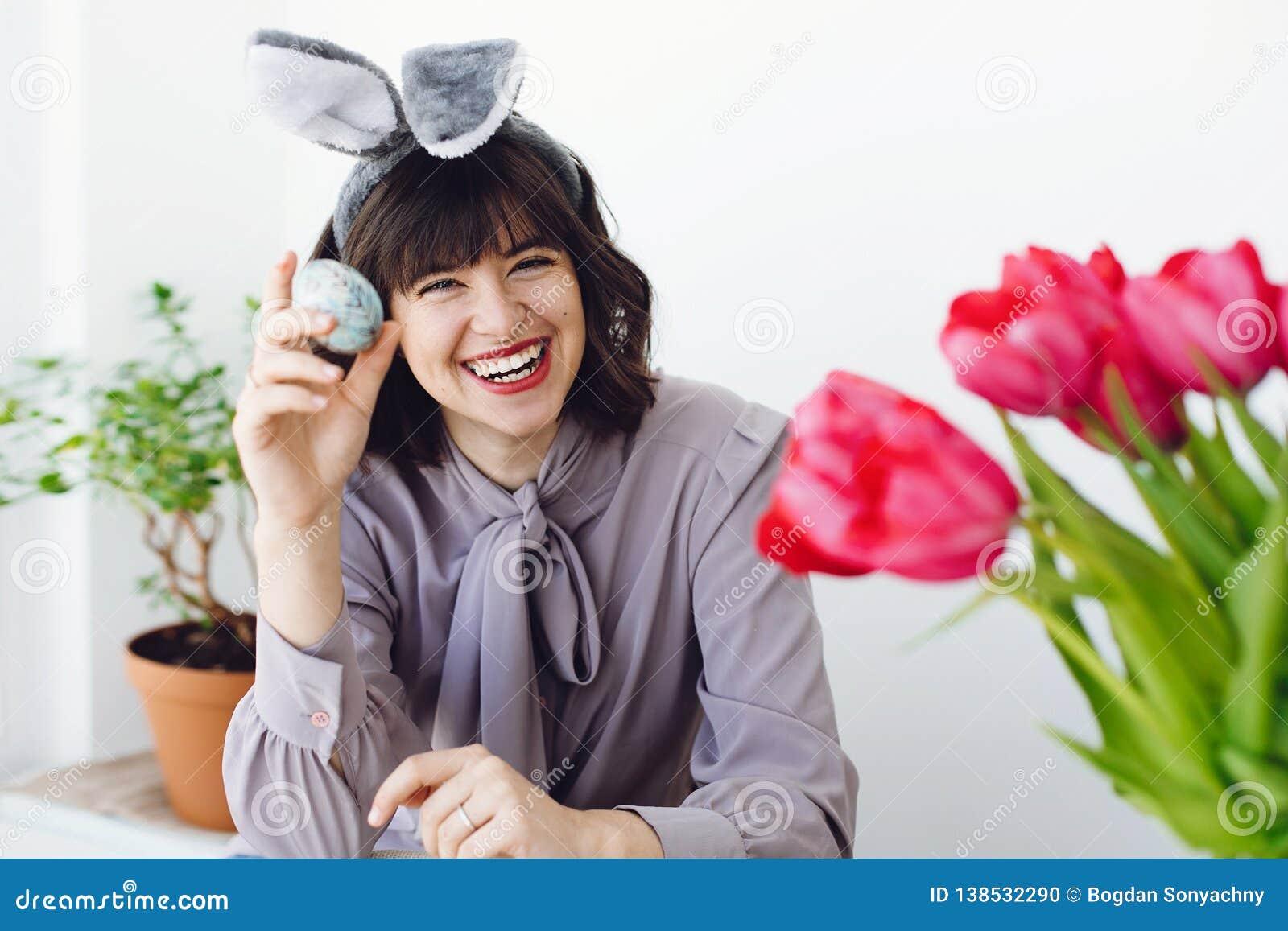 Belle jeune femme dans des oreilles de lapin peignant l oeuf de pâques et souriant à la table avec la peinture, brosses, tulipes