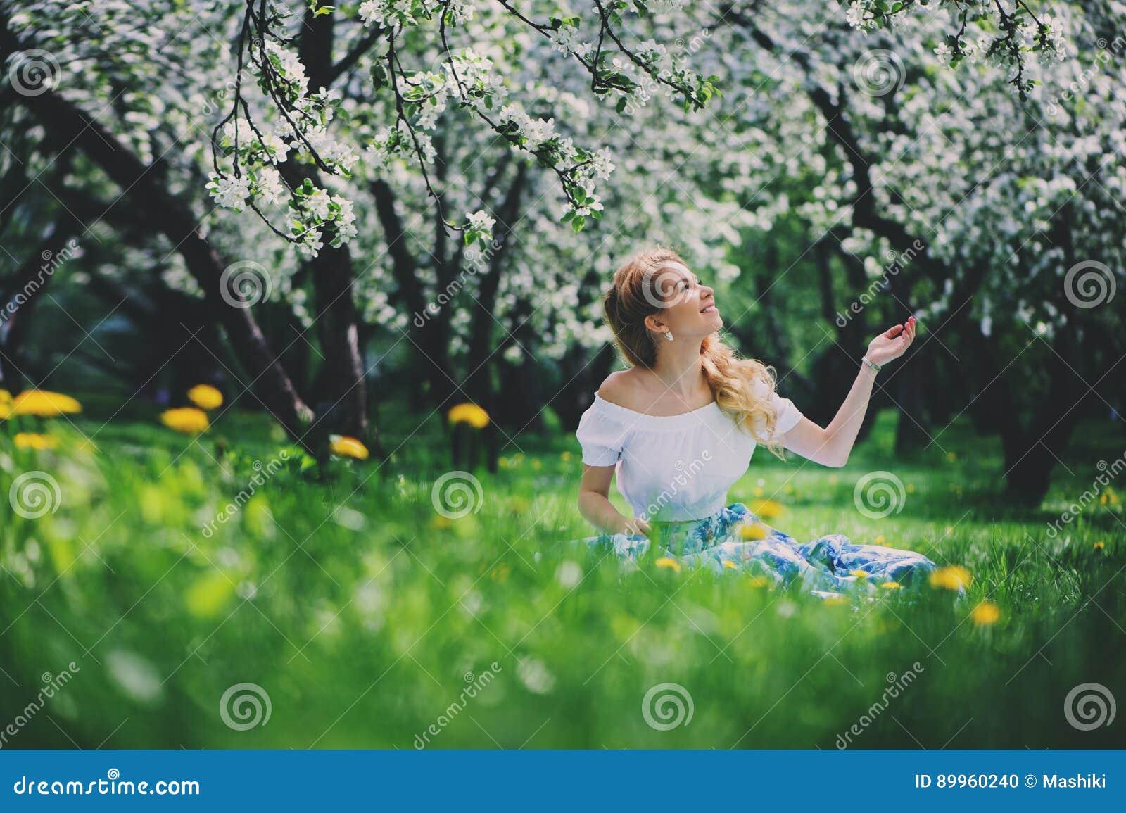 Belle jeune femme dans la maxi jupe florale marchant au printemps