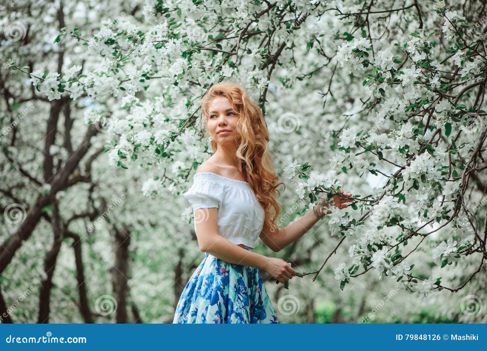 Belle jeune femme dans la maxi jupe florale marchant dans le jardin de floraison de ressort