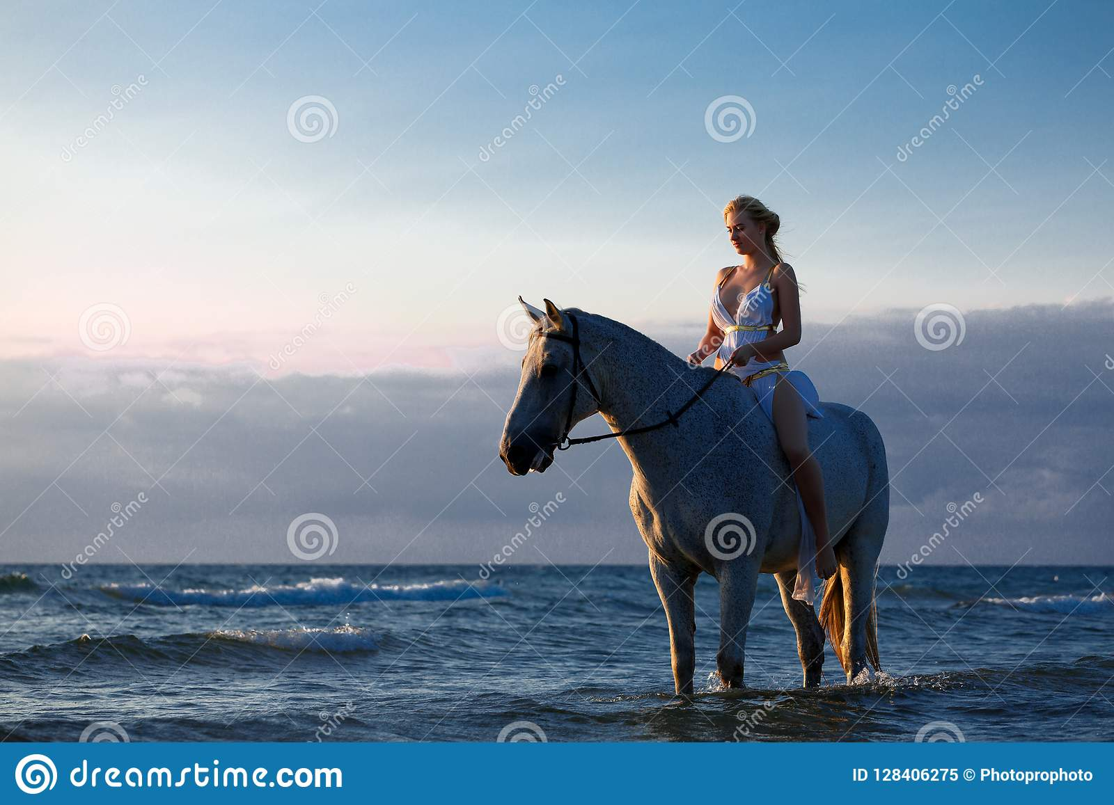 Belle jeune femme dans la robe blanche par la mer avec le cheval
