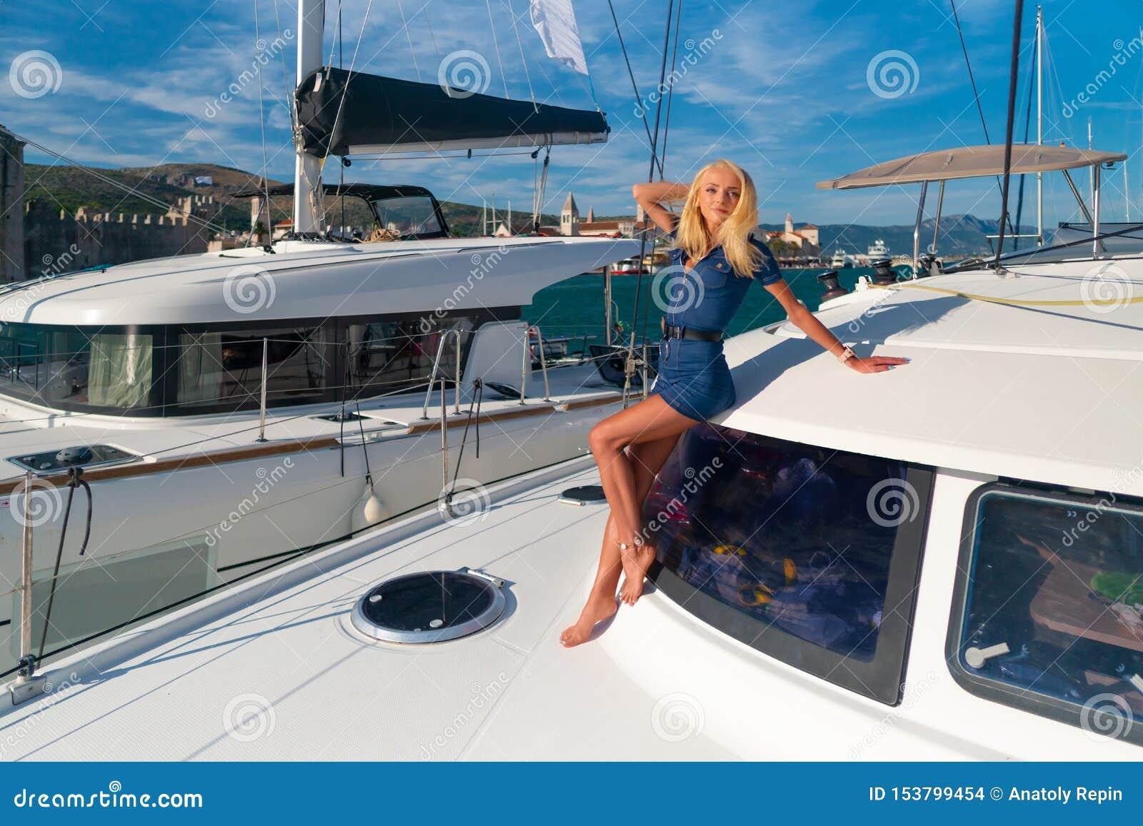 Belle jeune femme dans la tenue de détente se tenant sur un avant de yacht à la marina de Trogir, Croatie