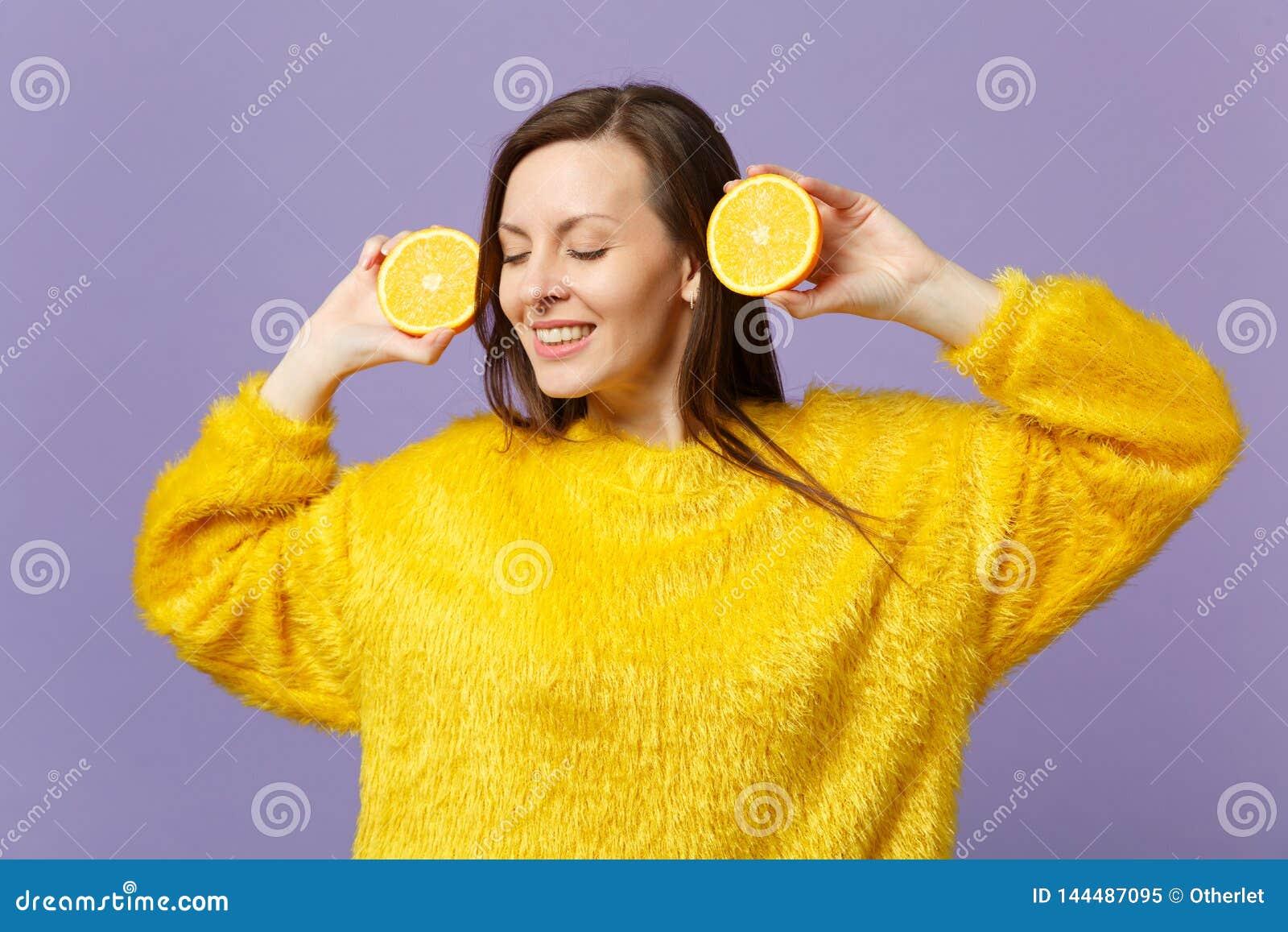 Belle jeune femme dans le chandail de fourrure maintenant des yeux fermés pour tenir des halfs du fruit orange mûr frais d isolem