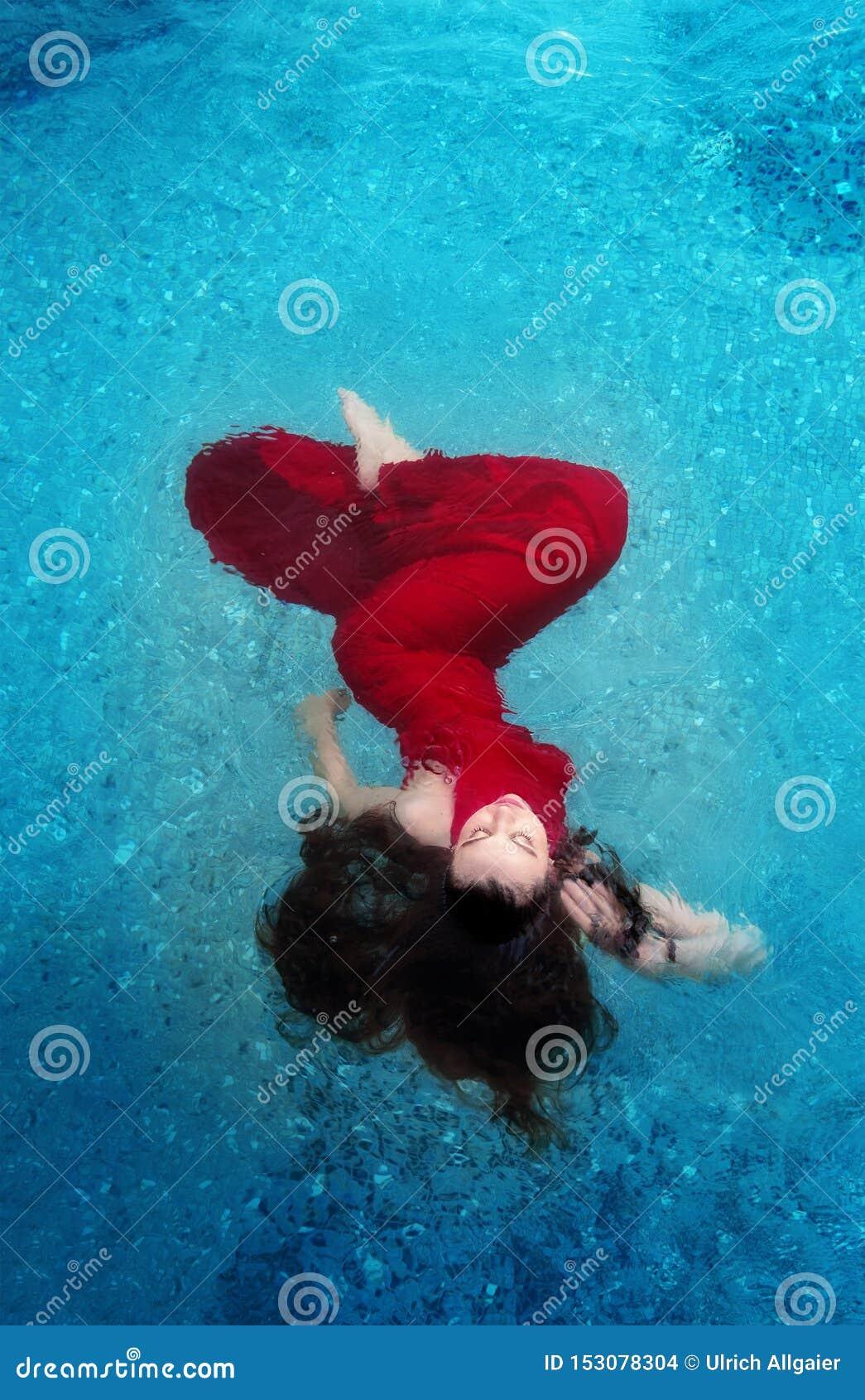 Belle jeune femme dans le flottement élégant rouge de robe égalisante léger dans l eau dans le flottement brun foncé de cheveux b
