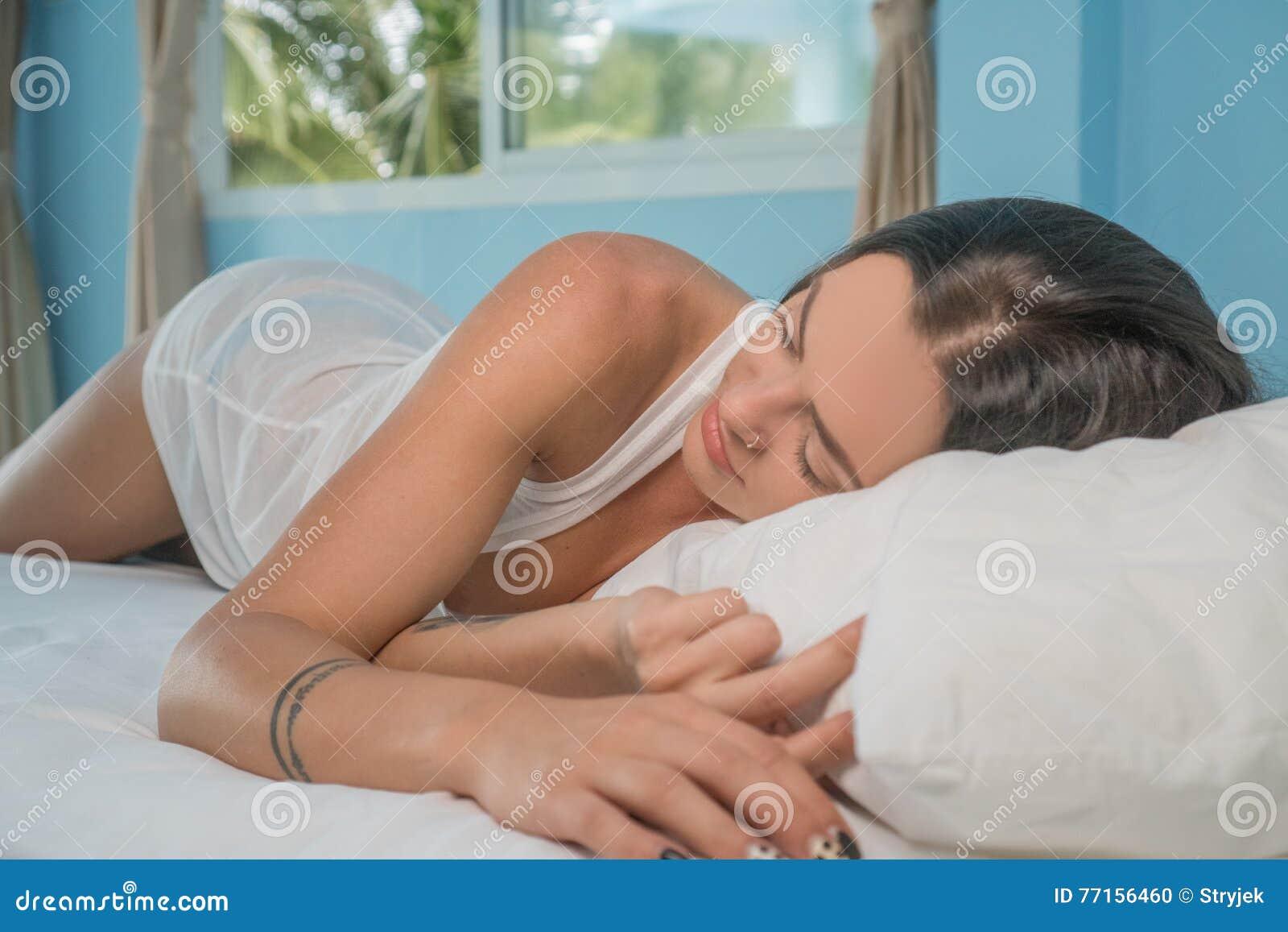 Belle jeune femme de brune dormant paisiblement se trouvant sur le lit