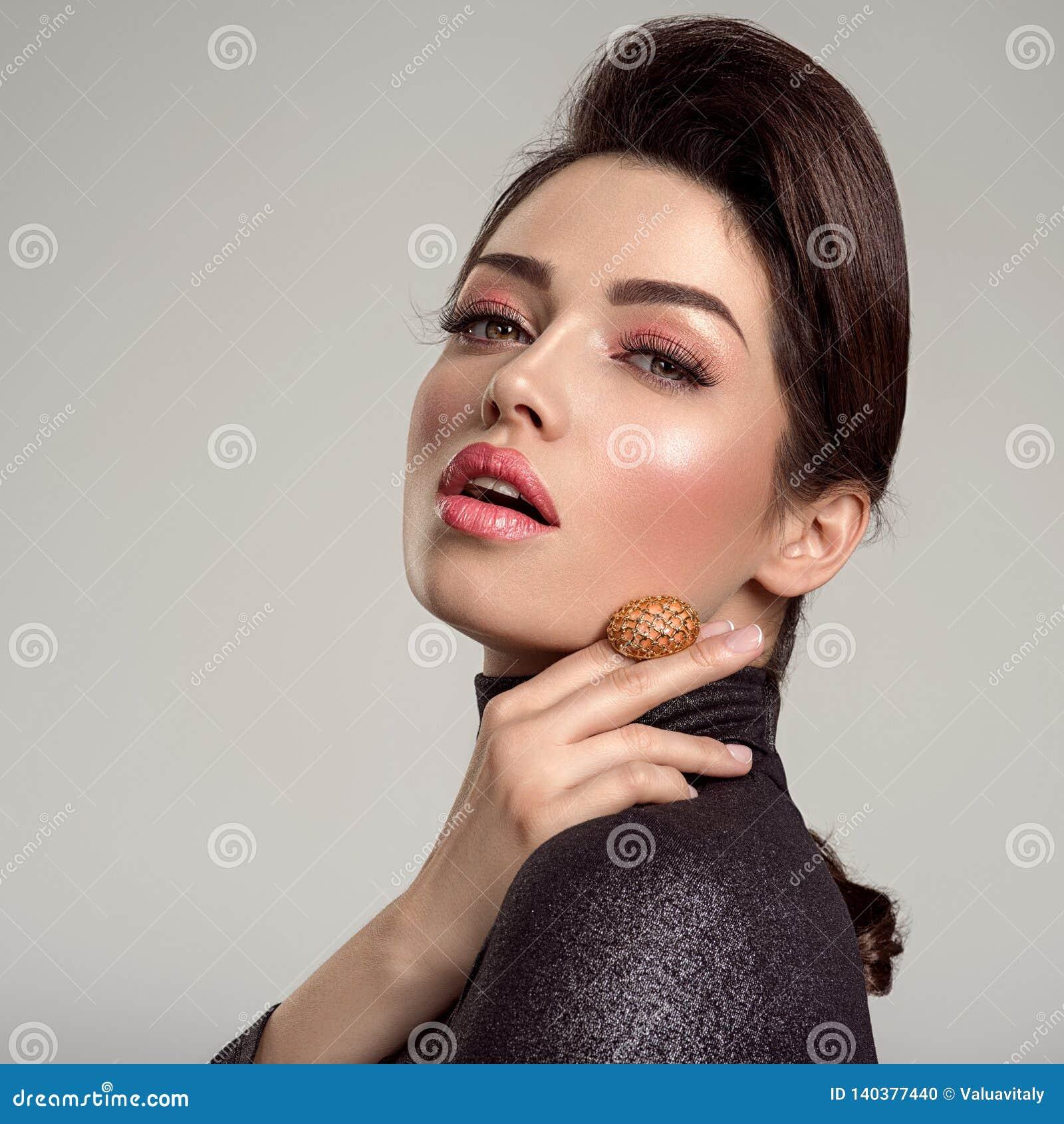 Belle jeune femme de mode avec le rouge à lèvres de corail vivant La fille blanche attirante porte les bijoux de luxe