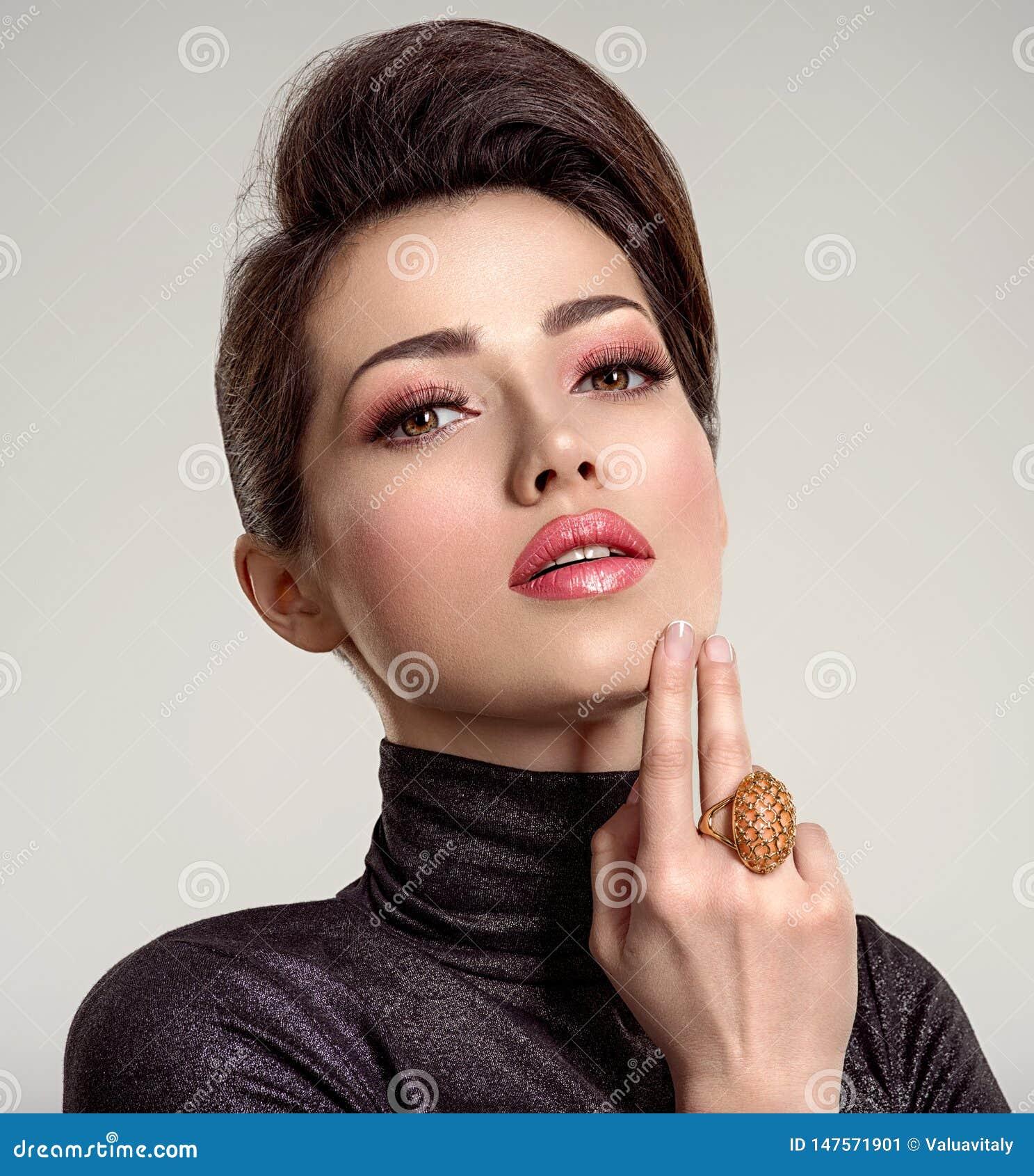 Belle jeune femme de mode avec le rouge ? l?vres de corail vivant La fille blanche attirante porte les bijoux de luxe
