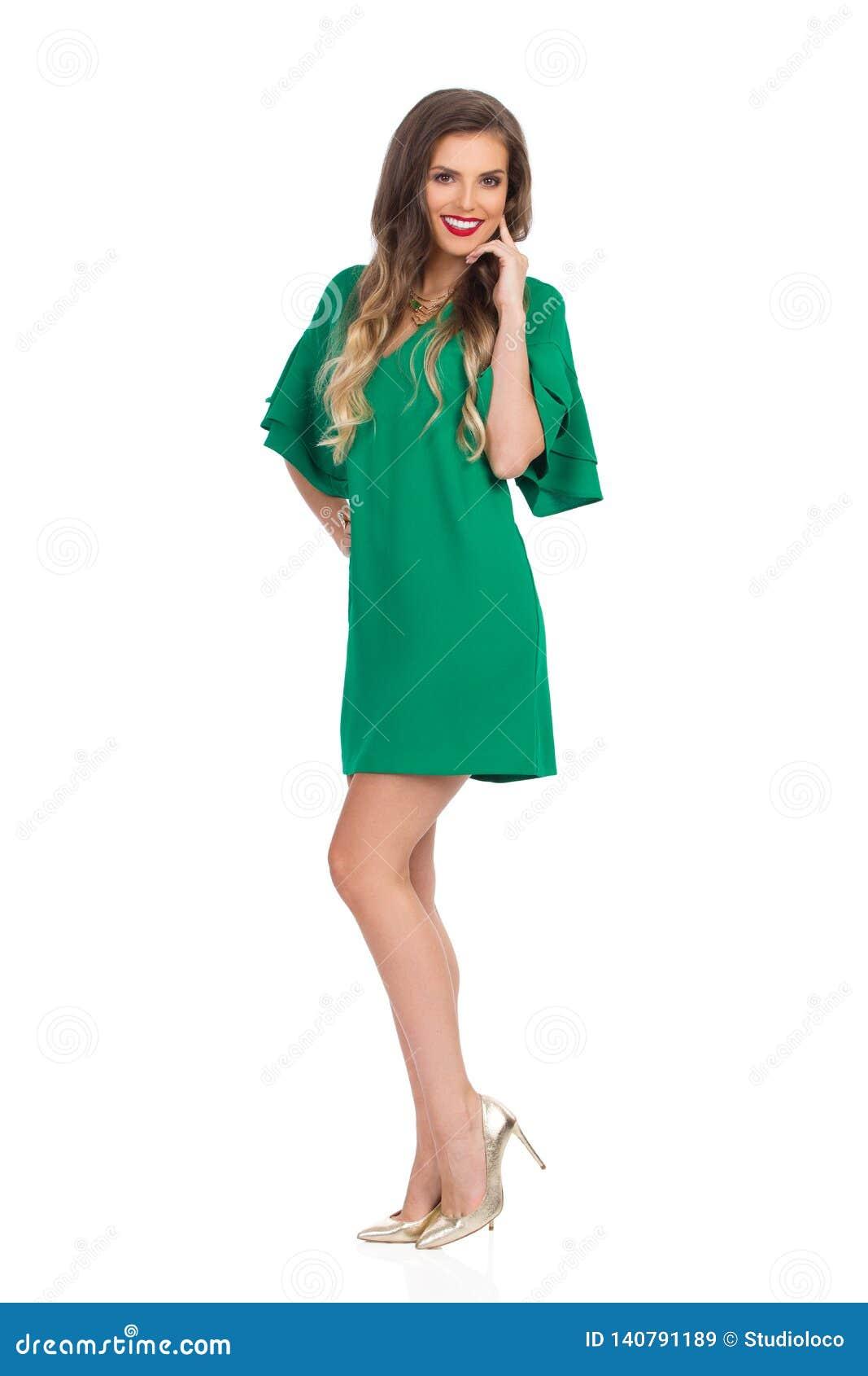 675898018df La belle jeune femme dans la mini robe et des talons hauts verts se tient