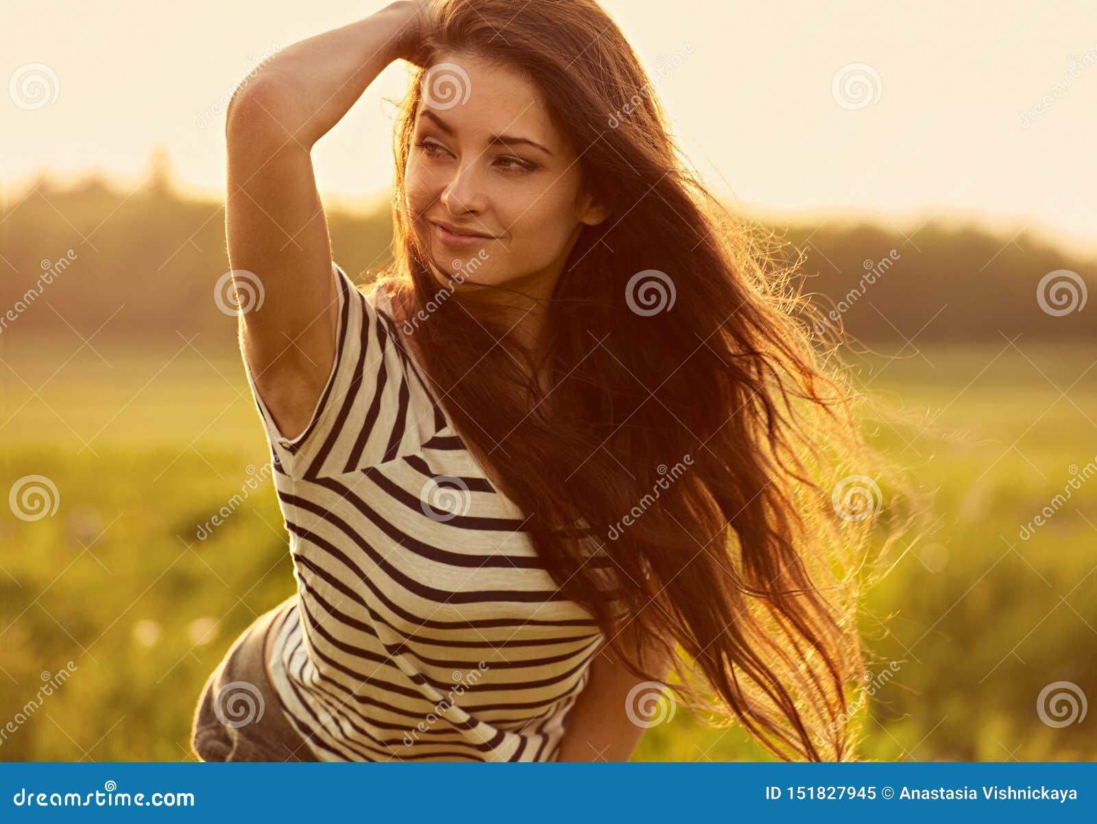 Belle jeune femme de sourire de pensée semblant heureuse avec de longs cheveux lumineux sur le fond d été de coucher du soleil de