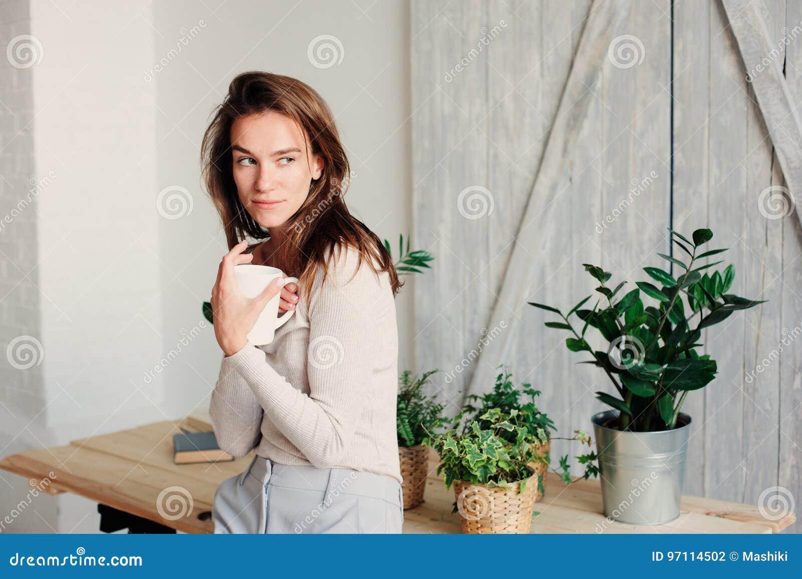 Belle jeune femme féminine détendant à la maison dans le matin paresseux de week-end avec la tasse de café