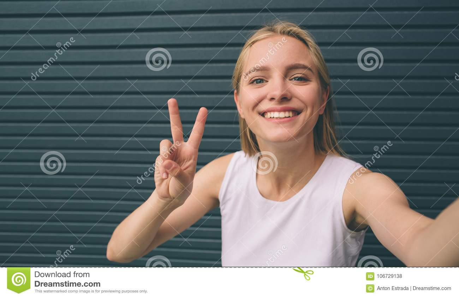 Belle jeune femme faisant l autoportrait sur un smartphone sur un fond de mur