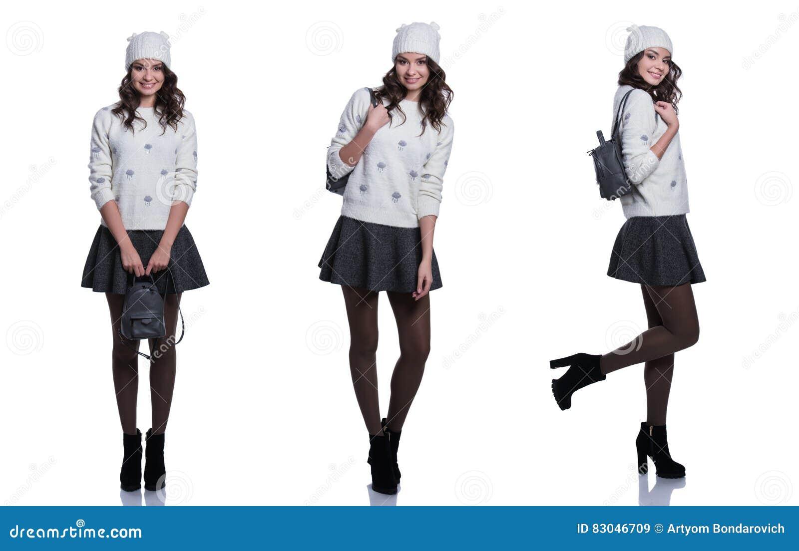 Belle jeune femme gaie utilisant le chandail, la jupe, le chapeau et le sac à dos tricotés D isolement sur le fond blanc