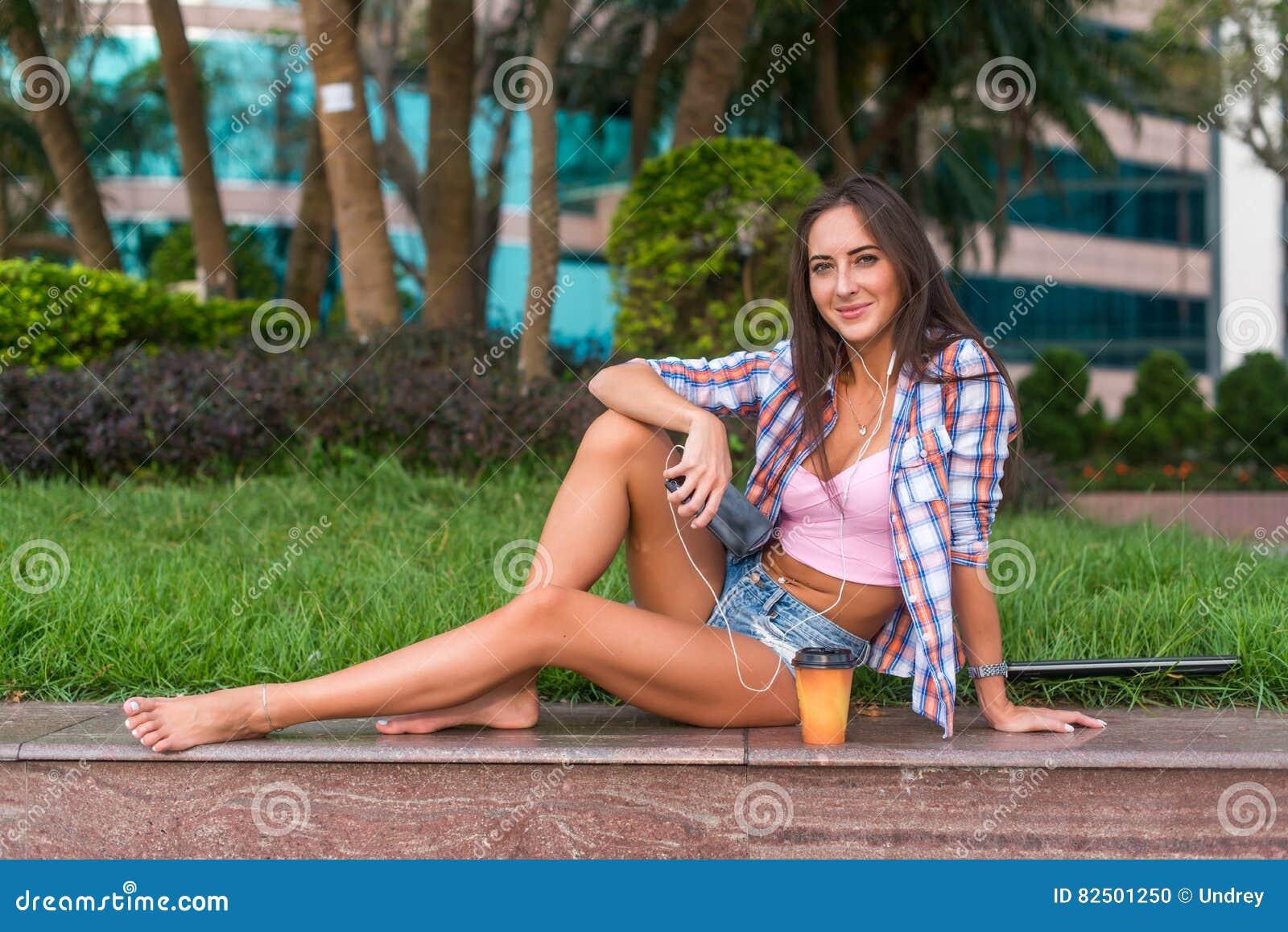 belle jeune femme heureuse avec les jambes nues se reposant sur la restriction en pierre en parc. Black Bedroom Furniture Sets. Home Design Ideas
