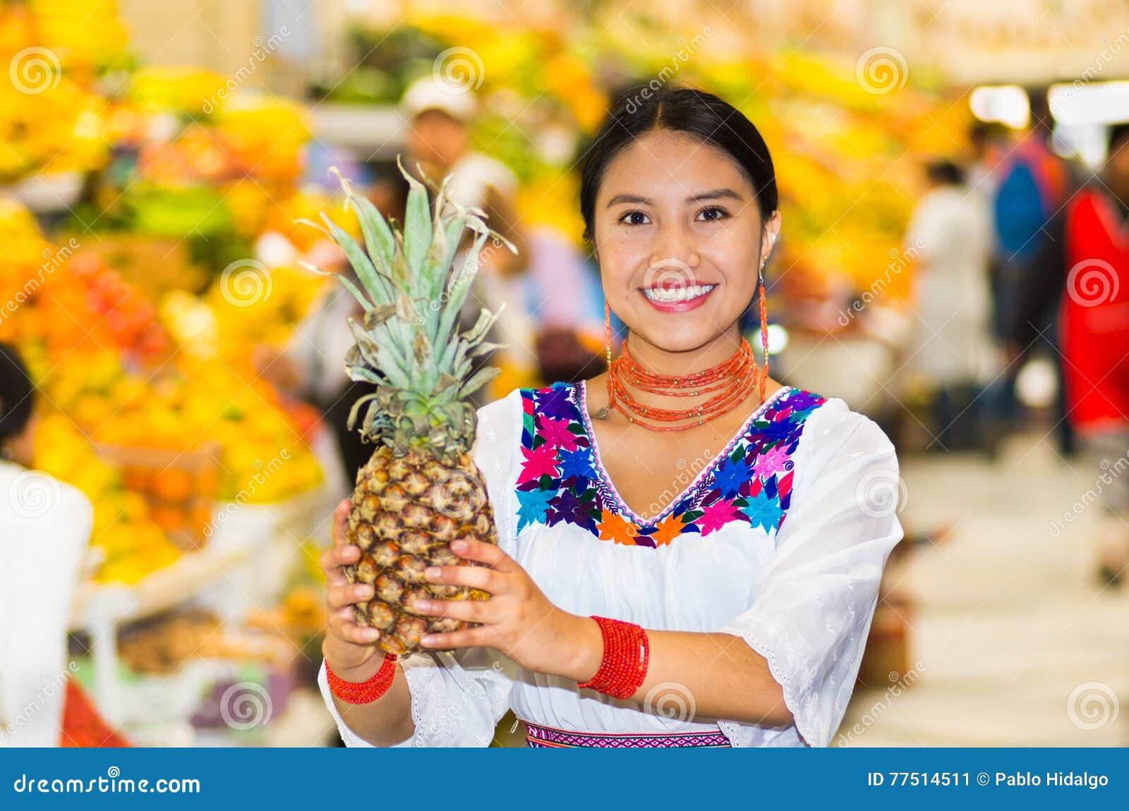 Belle jeune femme hispanique utilisant le chemisier traditionnel andin posant pour l appareil-photo tenant l ananas à l intérieur