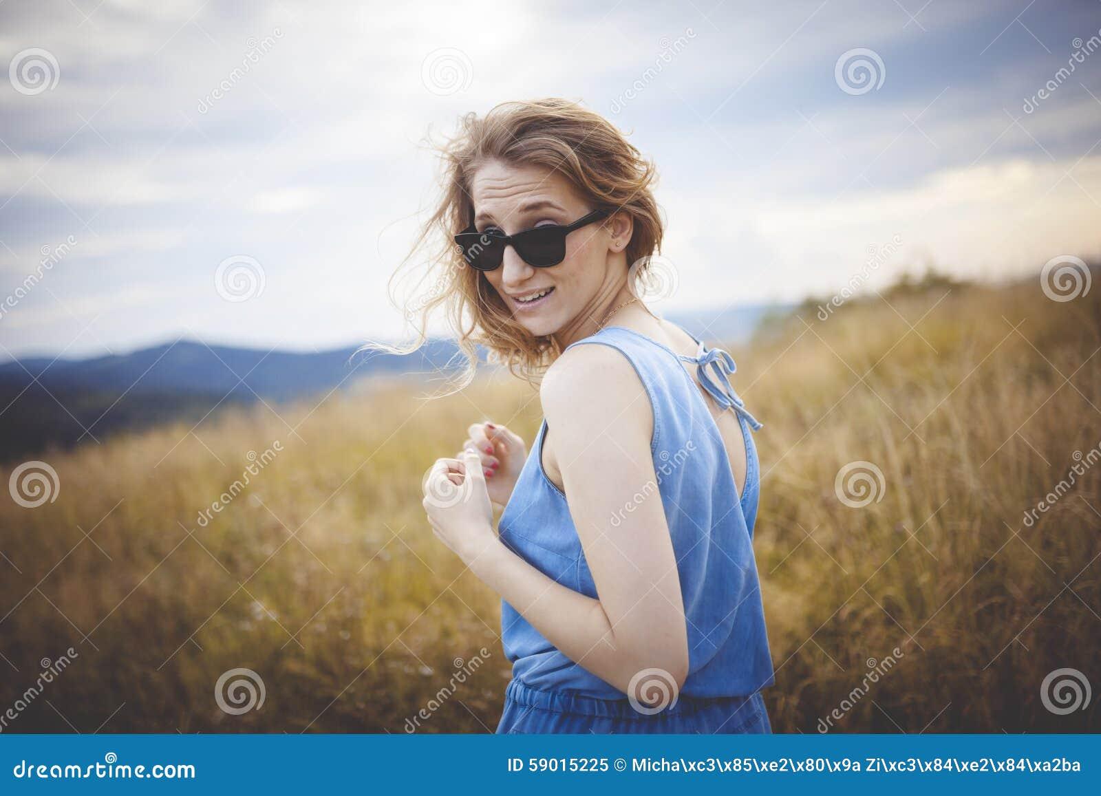 Belle jeune femme posant sur un pré