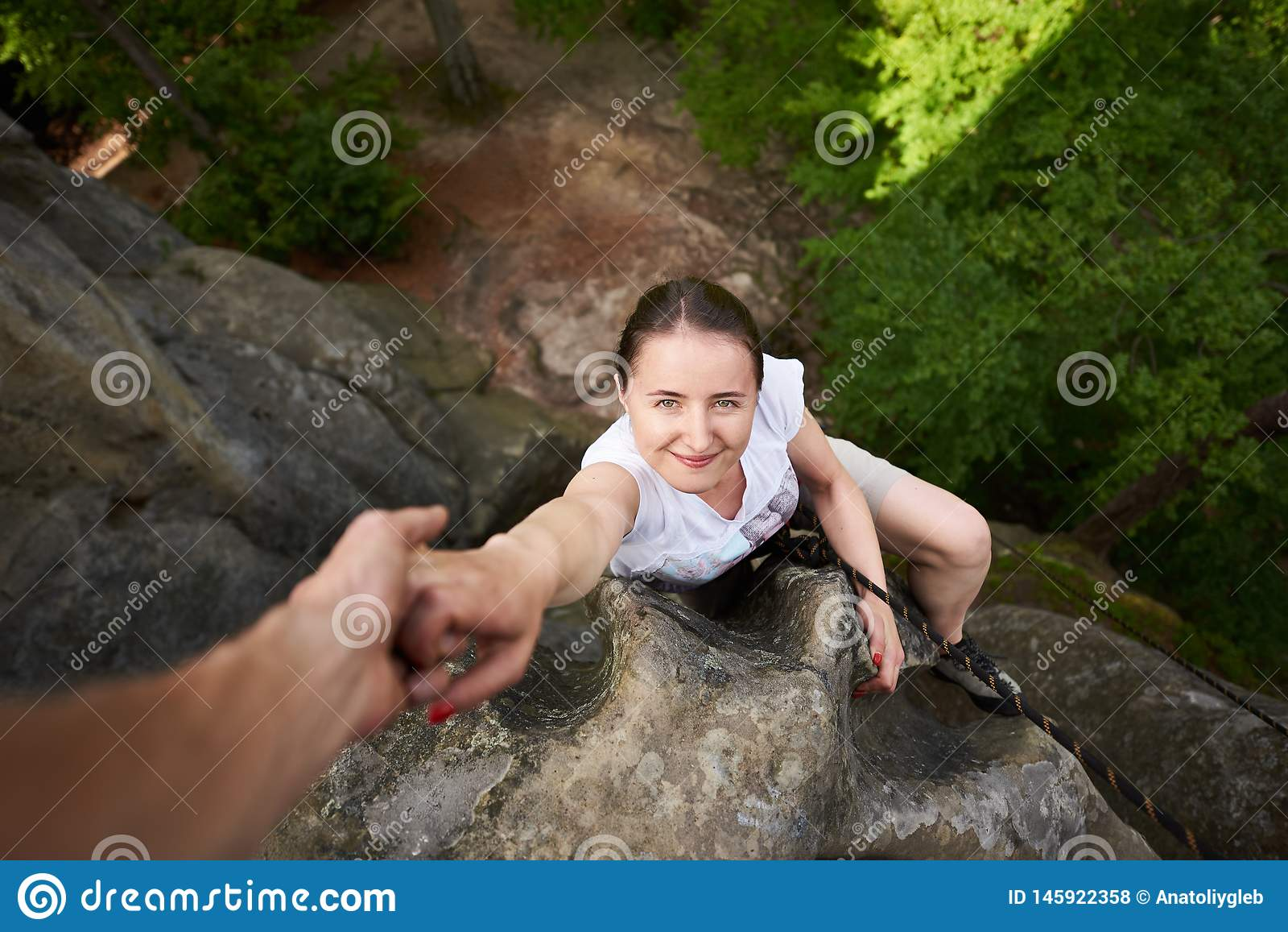 Belle jeune femme s élevant sur la roche dehors en été Vue sup?rieure Trekking s élevant de roche de fille heureuse dehors