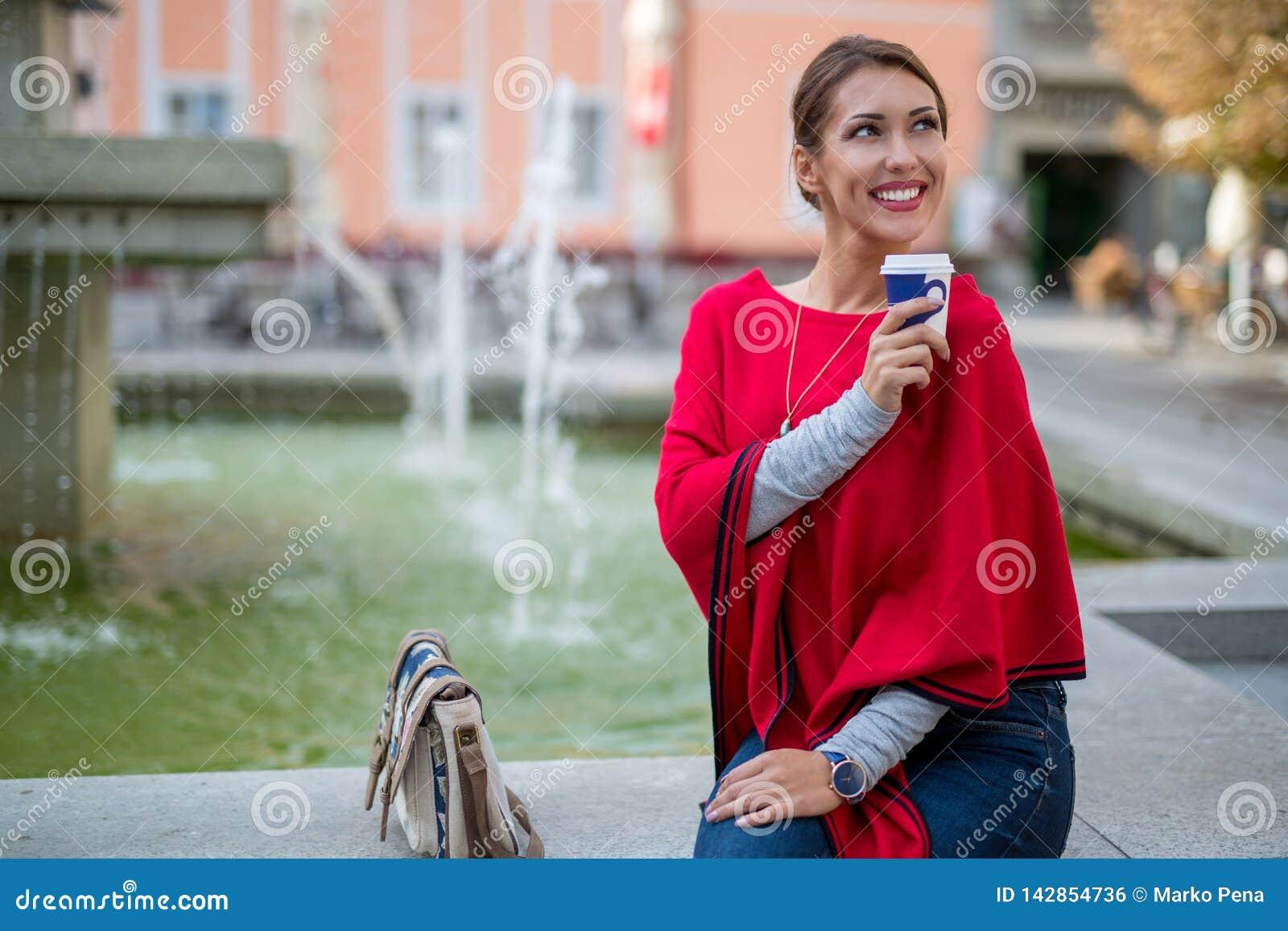 Belle jeune femme se reposant dehors à un puits tout en buvant du café