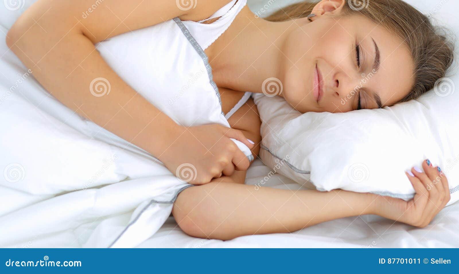 Belle jeune femme se situant dans le lit confortablement et avec bonheur