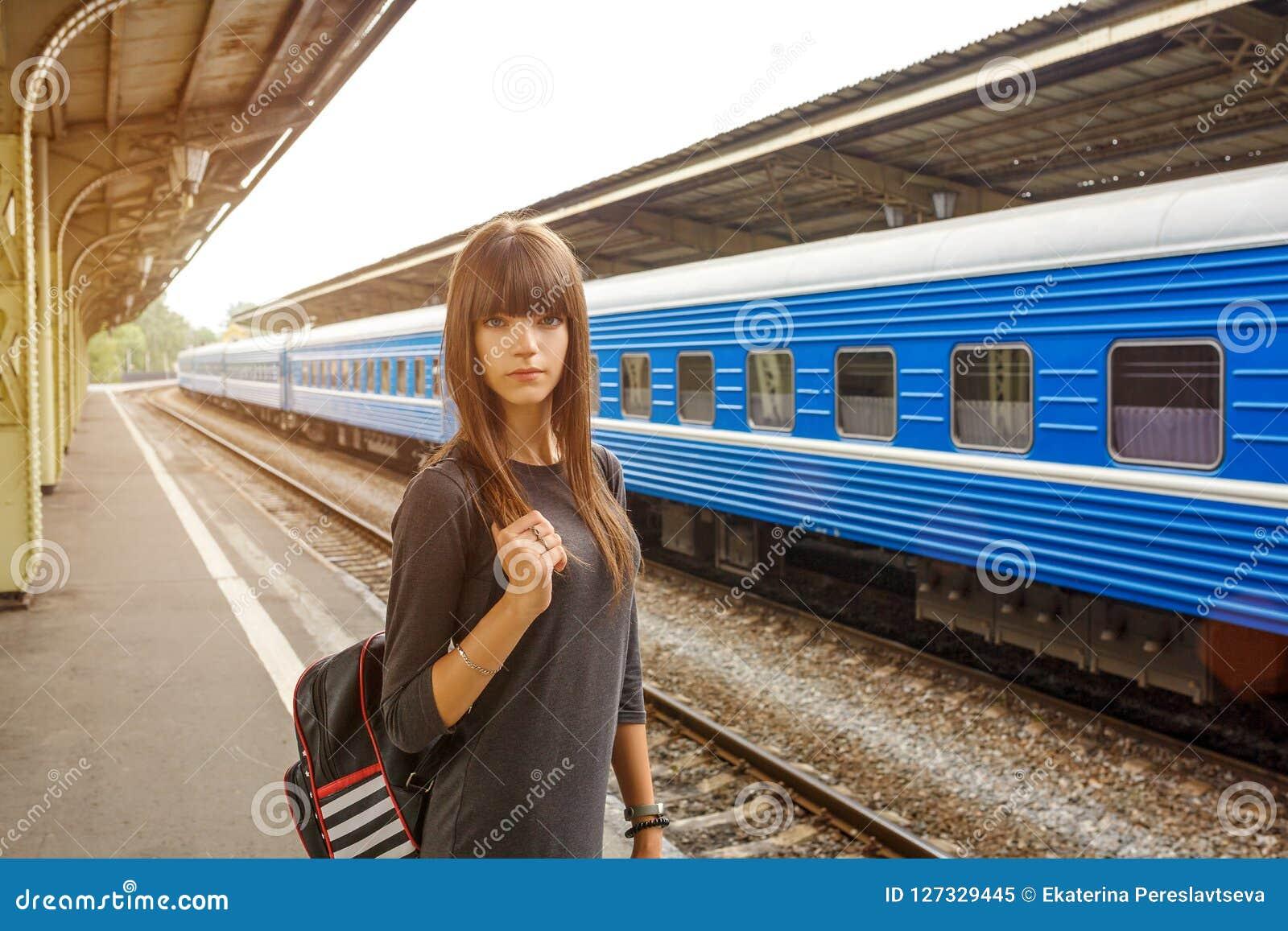 Belle jeune femme se tenant sur la plate-forme de la gare ferroviaire