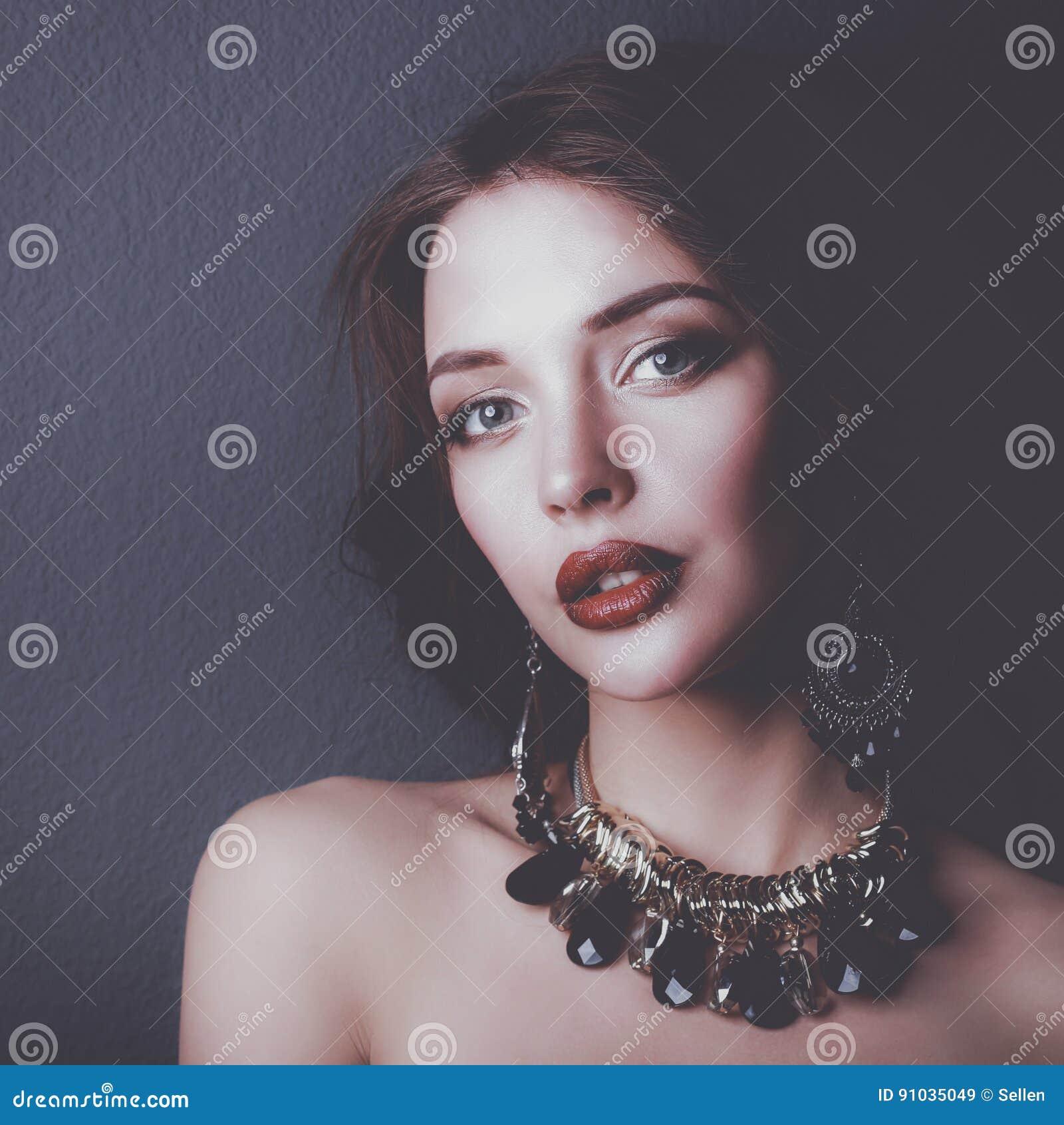 Belle jeune femme se tenant sur le fond gris