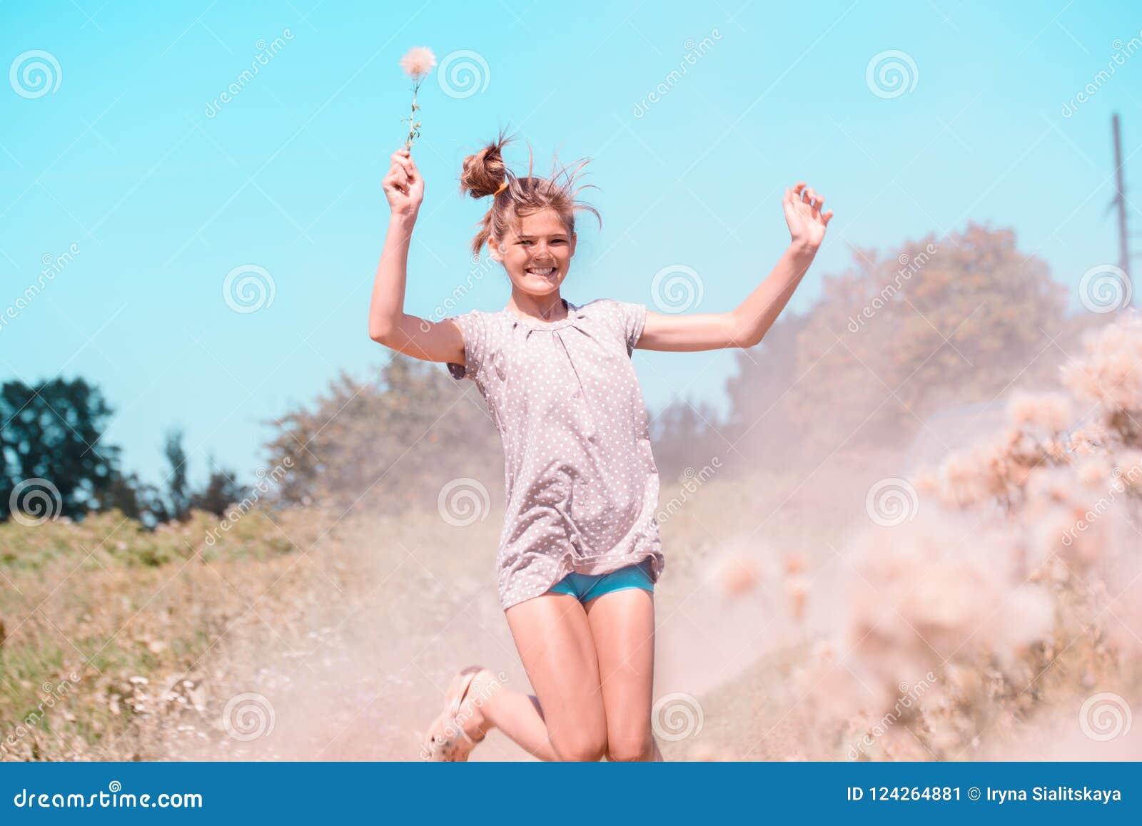 Belle jeune femme se trouvant sur le champ en herbe verte et pissenlit de soufflement outdoors Appréciez la nature Fille de souri