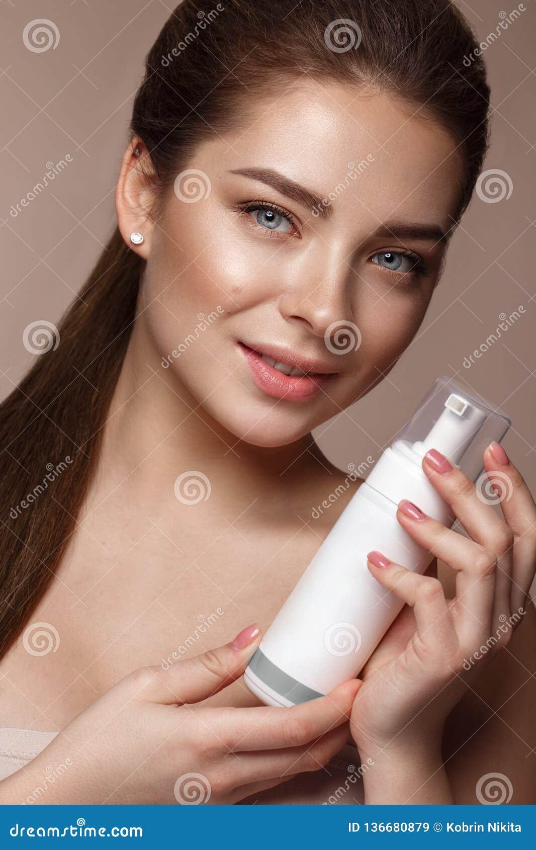 Belle jeune fille avec le maquillage nu naturel avec du cosmétique dans des mains Visage de beauté