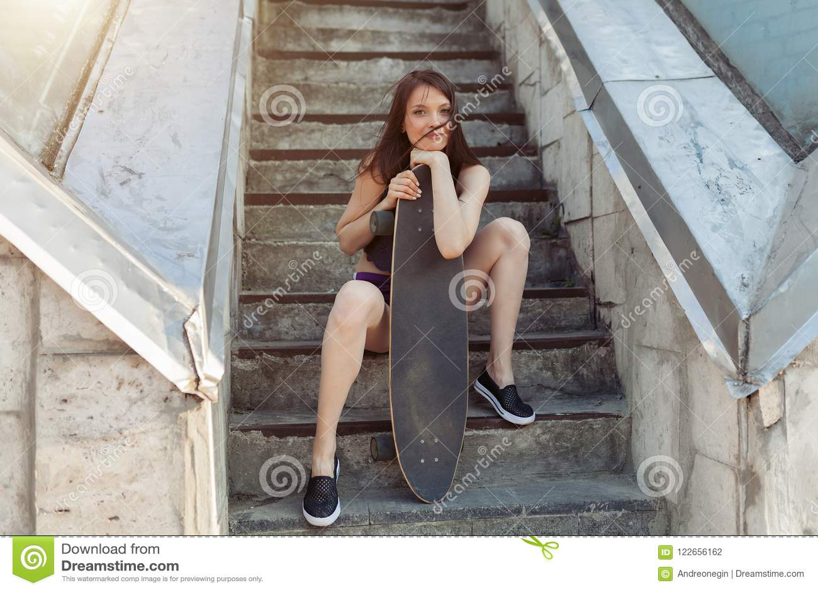 Belle jeune fille avec un long conseil dans la ville Le concept de la jeunesse moderne Vacances actives d amusement