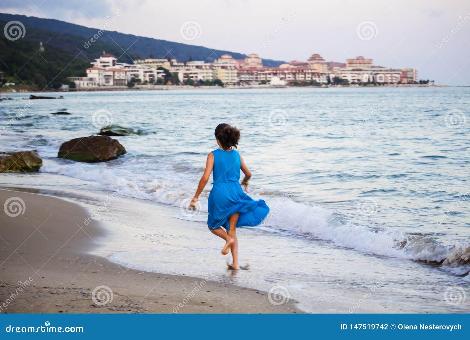 Belle jeune fille dans une robe bleue fonctionnant le long de la plage, brouillée
