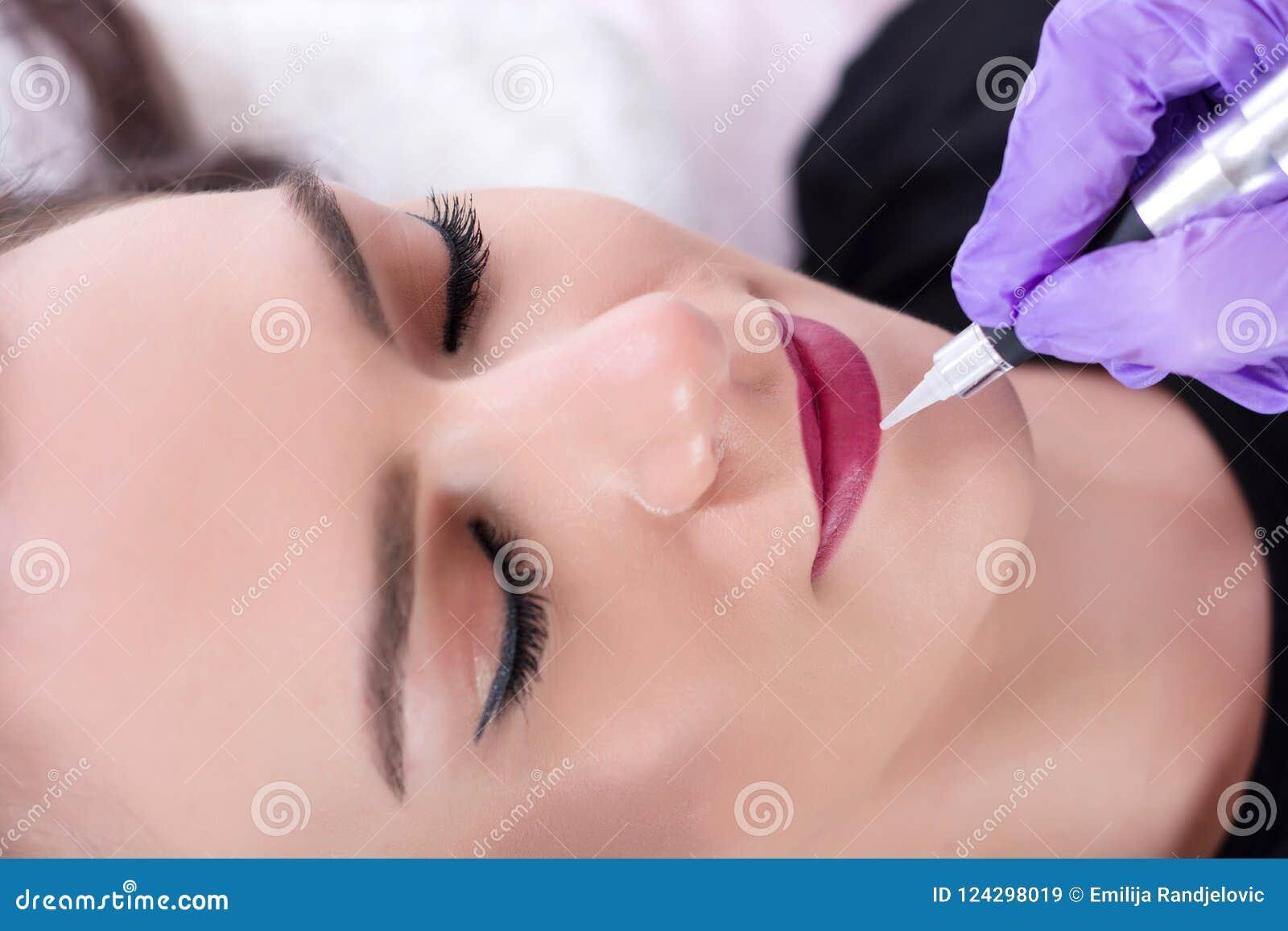 Belle jeune fille obtenant à tatouage les lèvres rouges dans le studio de beauté