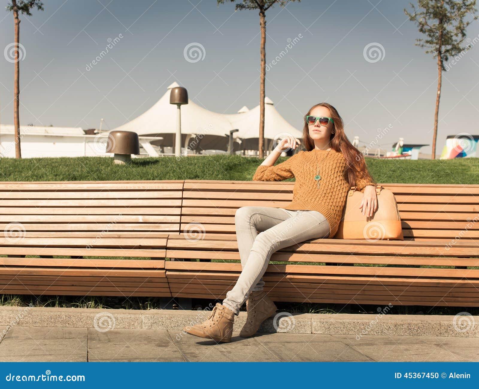 Belle jeune fille reposant sur un banc sur des whis chauds d un jour d été un sac