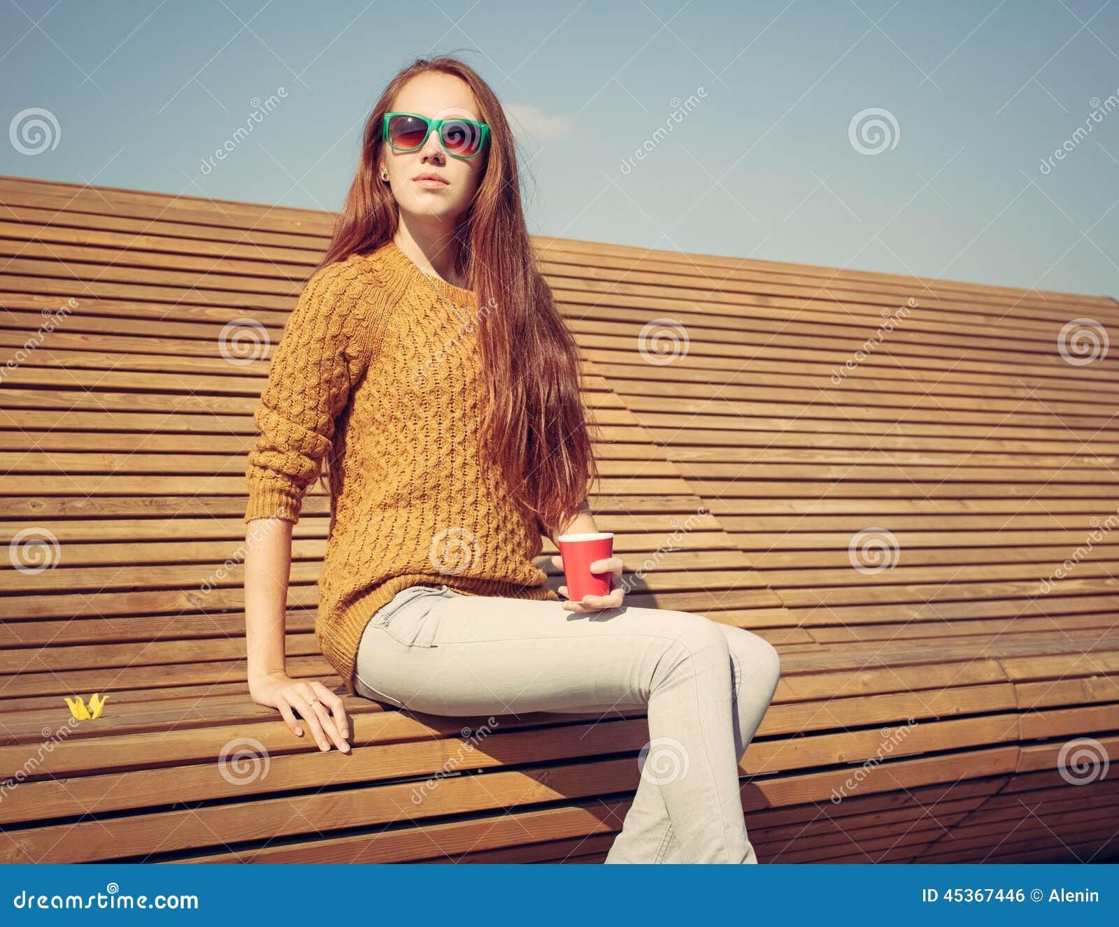 Belle jeune fille s asseyant sur un banc sur un cuo chaud de whis de jour d été de café