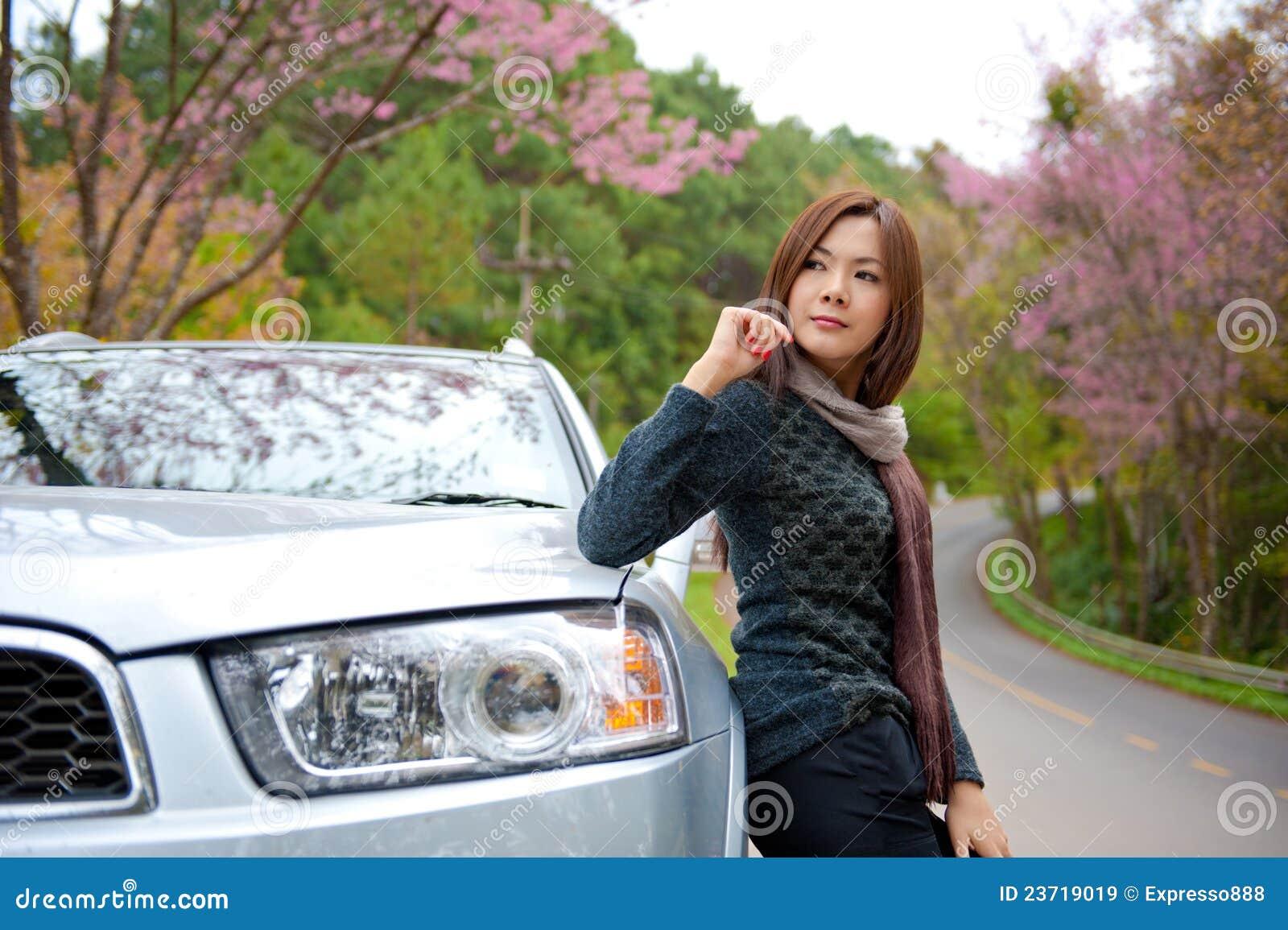 Belle jeune fille se reposant sur le côté de son véhicule