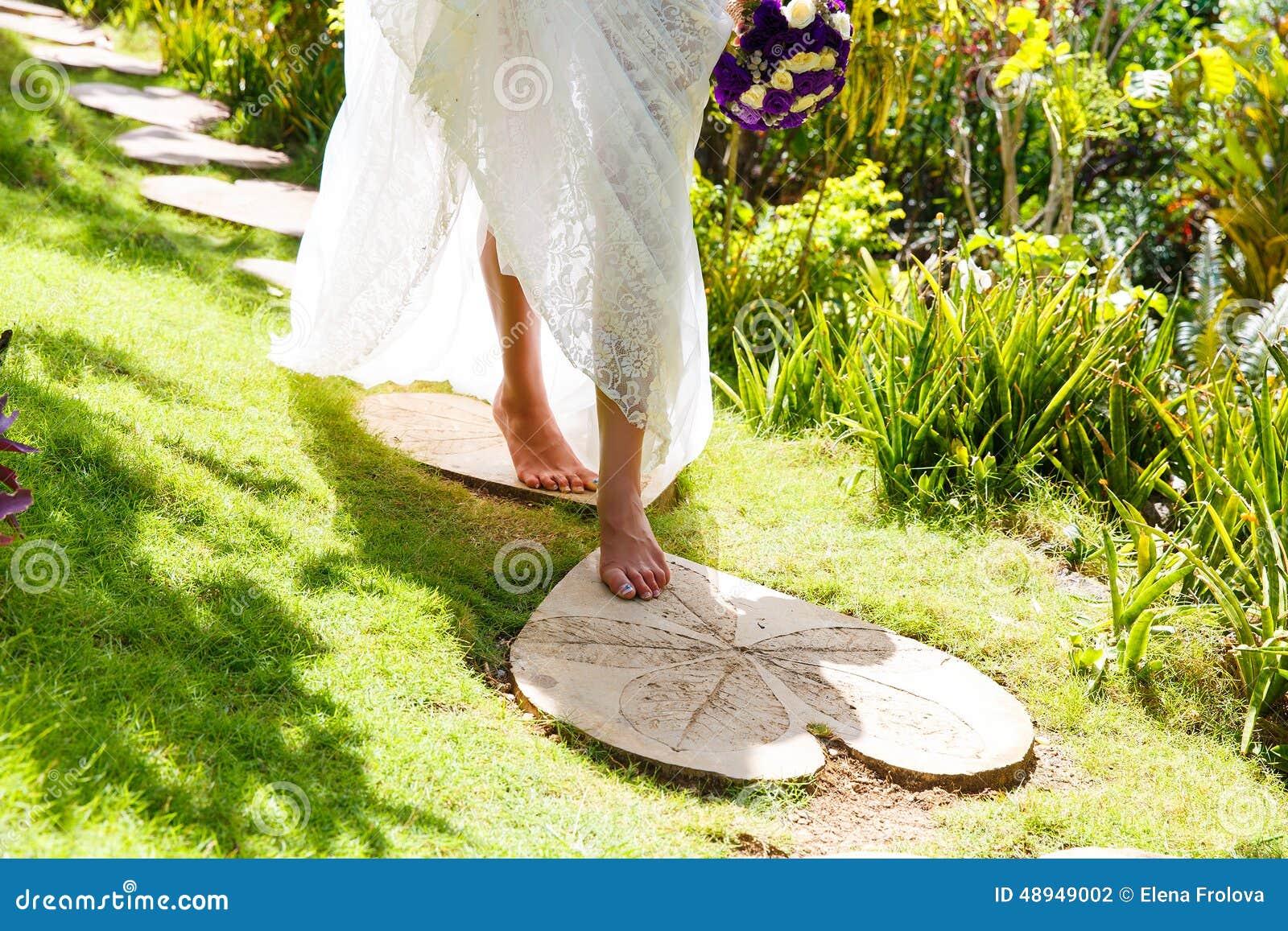 Belle jeune jeune mariée dans une robe de mariage blanche avec le bouquet dans h