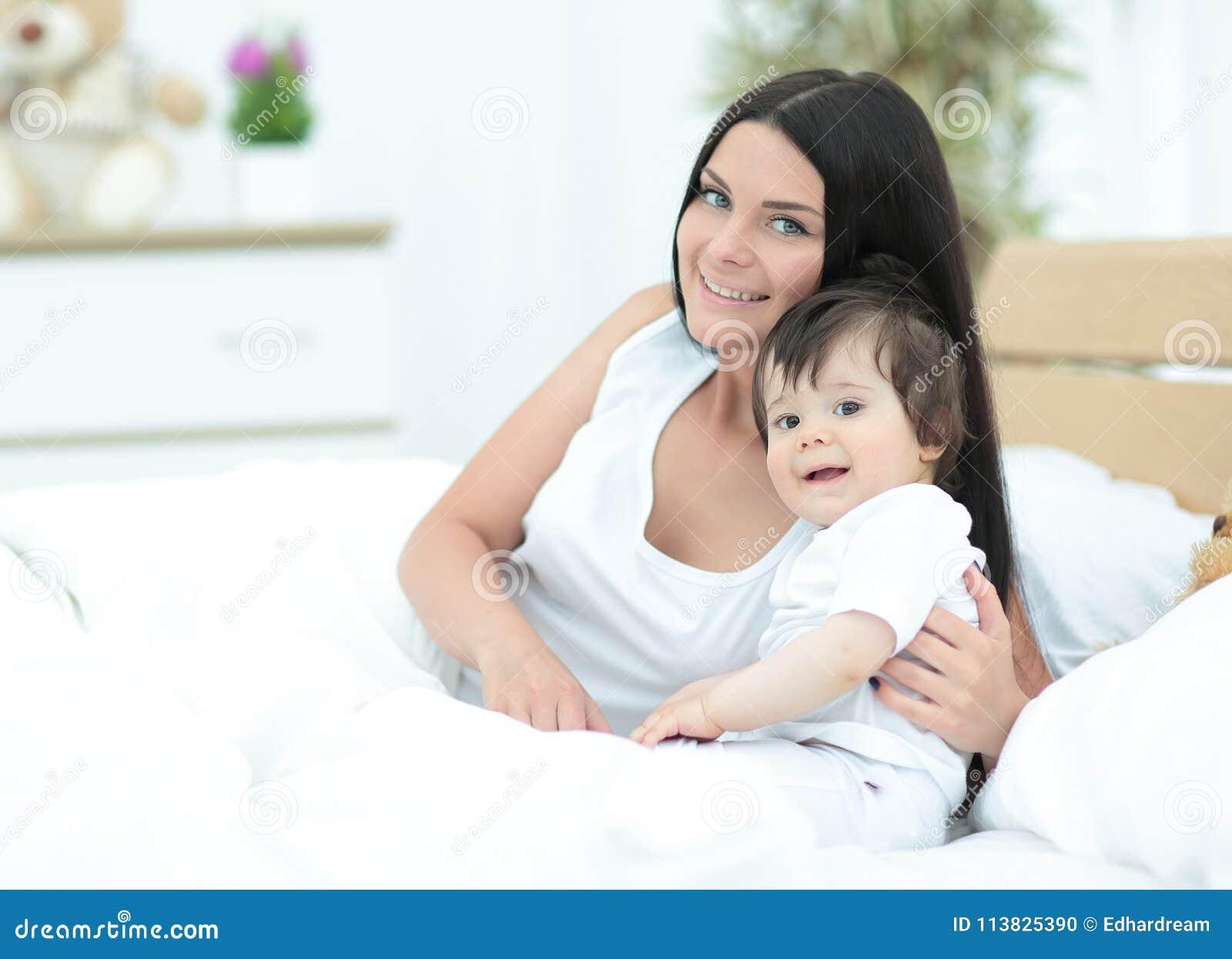 Belle jeune mère avec un bébé se situant dans le lit et le sourire